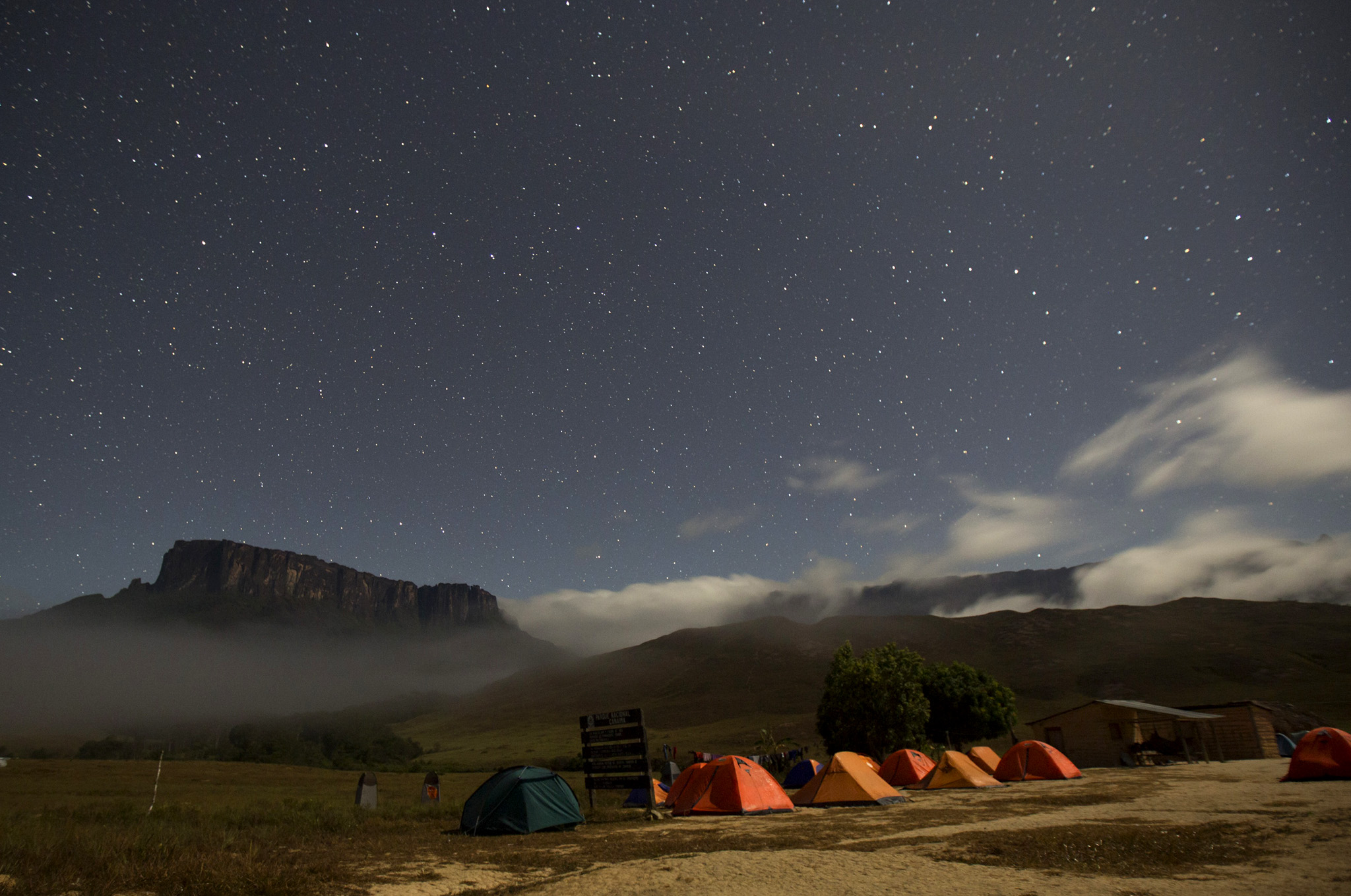 "Kukenan and Roraima mounts are seen from the Tec Camp, near Venezuela's border with Brazil...Kukenan (L) and Roraima mounts are seen from the Tec Camp, near Venezuela's border with Brazil January 14, 2015. A mysterious table-topped mountain on the Venezuela-Brazil border that perplexed 19th century explorers and inspired ""The Lost World"" novel is attracting ever more modern-day adventurers. Once impenetrable to all but the local Pemon indigenous people, now several thousand trekkers a year make the six-day hike across Venezuela's savannah, through rivers, and up a narrow path that scales Mount Roraima's 600-meter cliff-faces. While that is a help to Venezuela's tottering tourism industry and brings revenues to local communities, it is also scattering a prehistoric landscape with unwanted litter.    REUTERS/Carlos Garcia Rawlins"