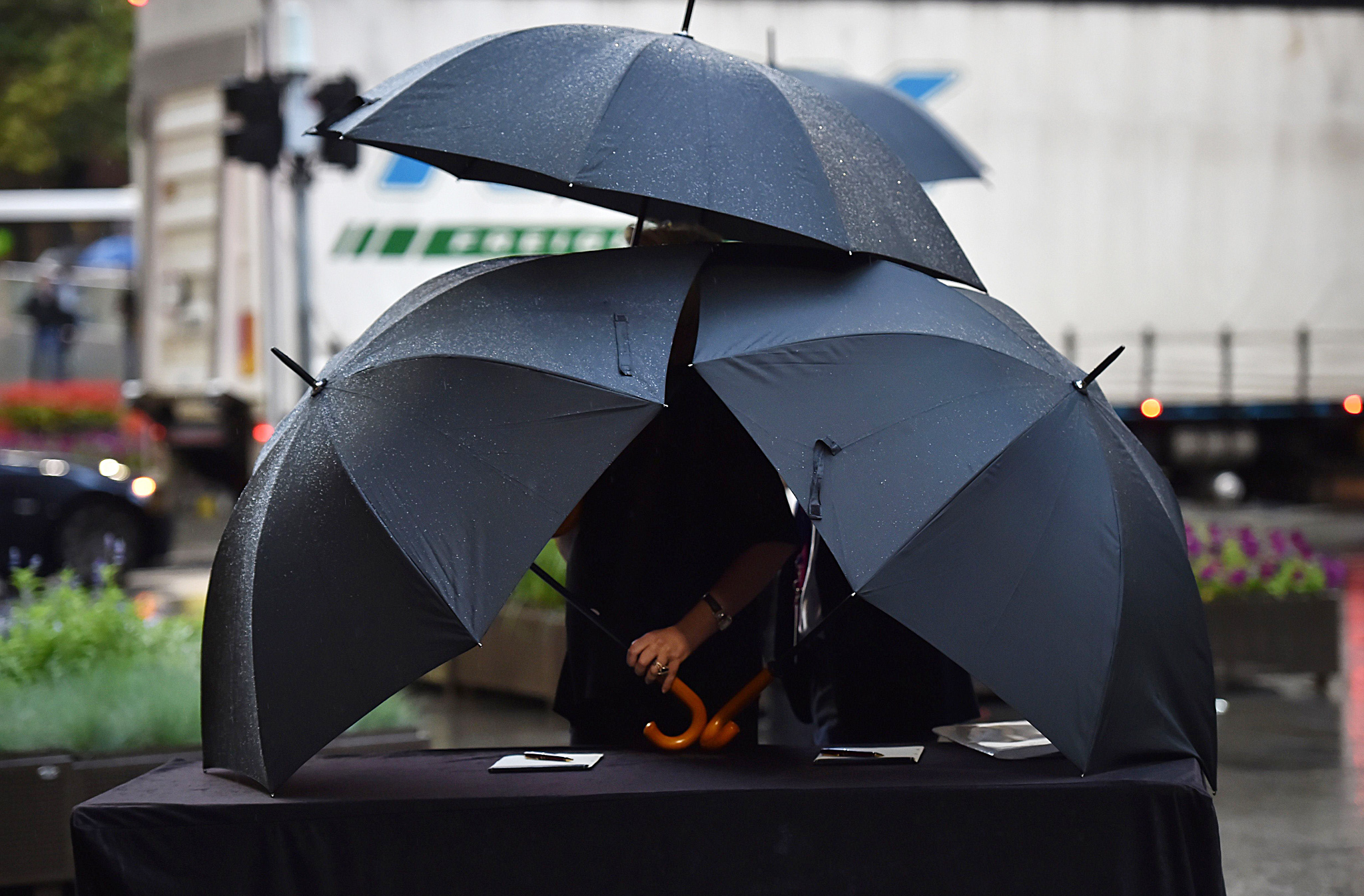 TOPSHOTS Umbrellas protect condolence bo...TOPSHOTS Umbrellas protect condolence books for victims of the siege at the Lindt Cafe where three people, including the lone gunman, died in December 2014, from the rain before being signed by visiting British foreign and defence secretaries in Sydney on February 2, 2015. The visit to the site was held ahead of annual Australia-UK security talks. AFP PHOTO / Peter PARKSPETER PARKS/AFP/Getty Images