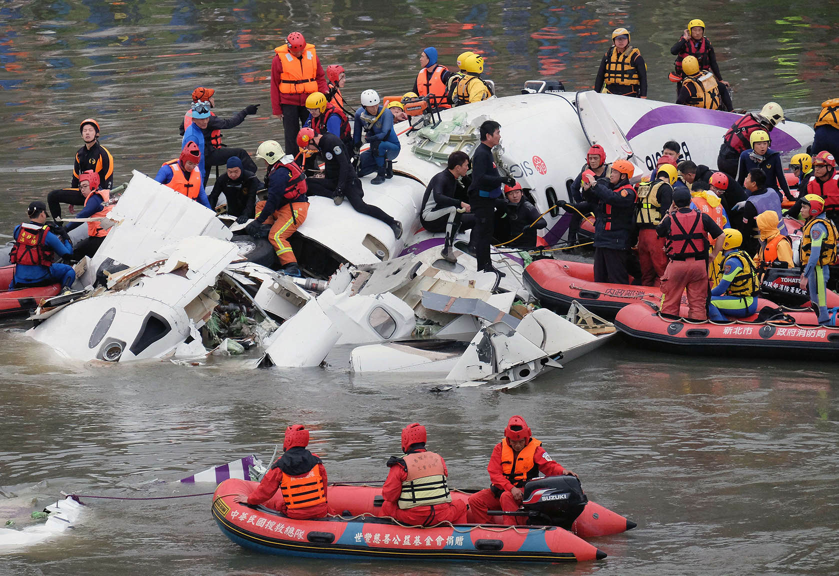 Rescue personnel search for passengers from the wreckage of a TransAsia ATR 72-600
