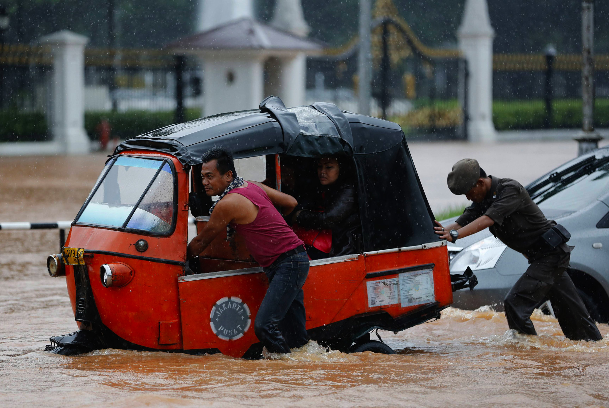 A driver pushes his Baja vehicle through flood waters outside the Presidential Palace, after heavy seasonal rains flooded parts of Jakarta, Indonesia.