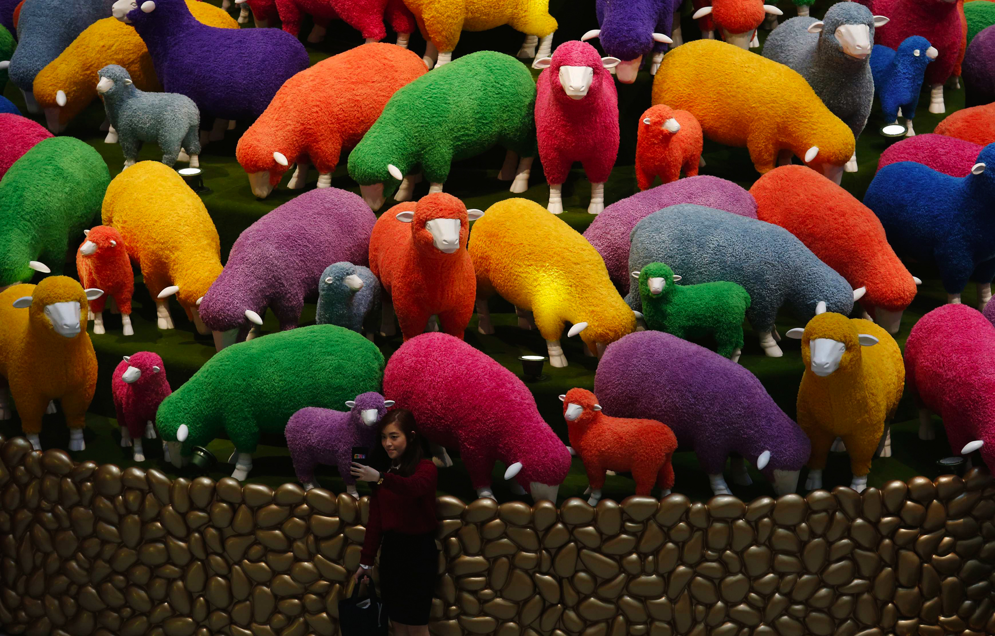 A woman takes a selfie in front of a Lunar New Year display featuring sheep at a shopping mall in Hong Kong.