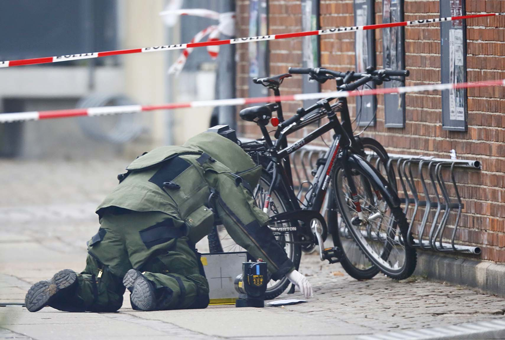 A bomb disposal expert investigates an unattended package at a cafe in Copenhagen