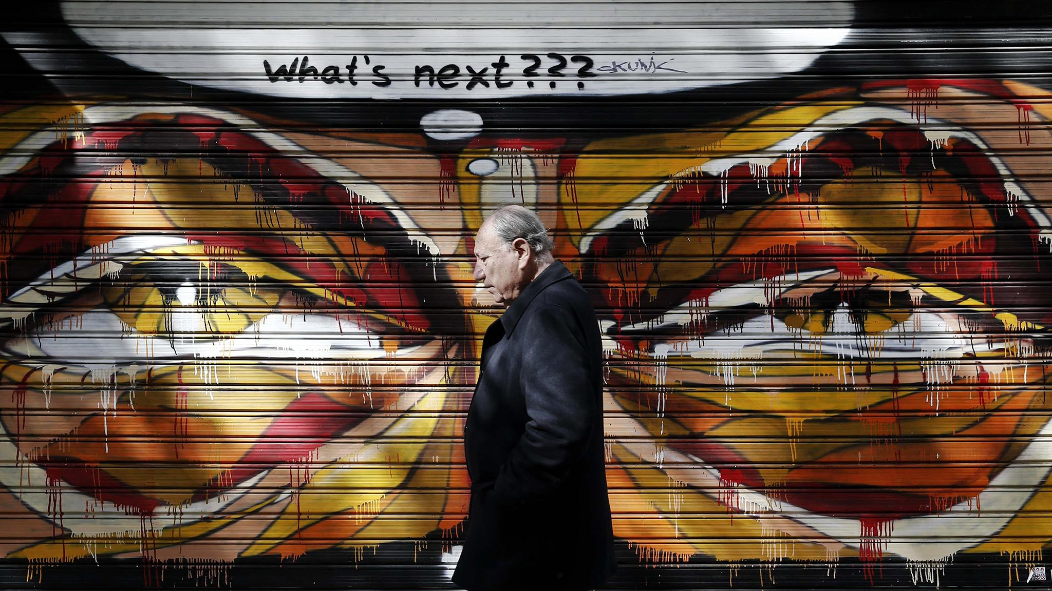 A man walks past graffiti in Athens