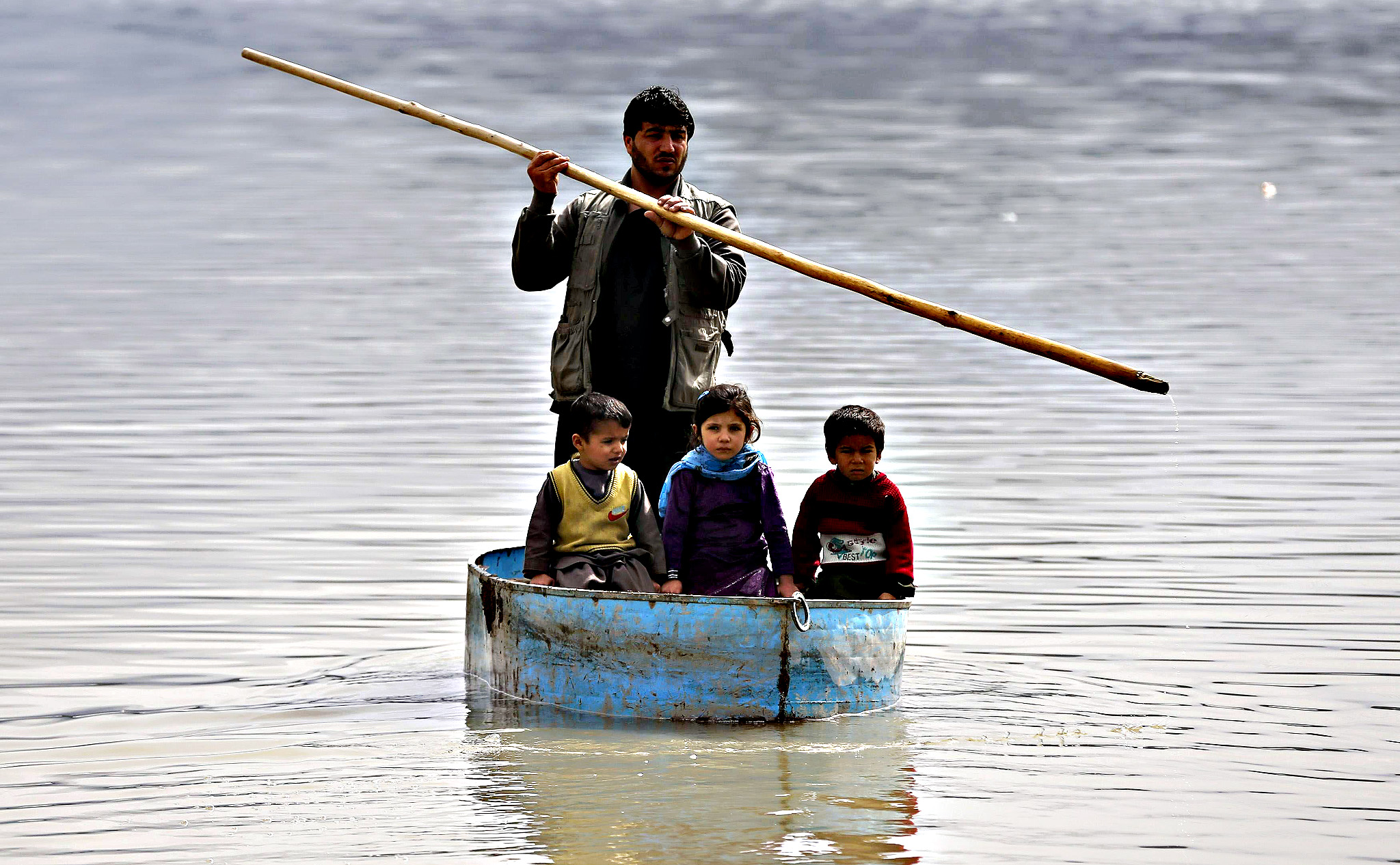 Afghan children sail on a homemade boat in a lake on the outskirts of Kabul, February 24, 2015. Each ride costs 50 Afghanis ($0.87), according to the boatman.