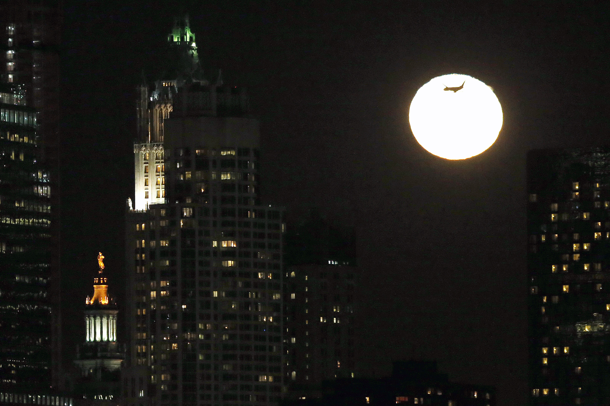An airplane flies past the rising moon in its waning gibbous stage as viewed from Jersey City, N.J., Thursday, Feb. 5, 2015. The statue known as Civic Fame, bottom left, which stands atop of the Manhattan Municipal Building in New York, is also visible.
