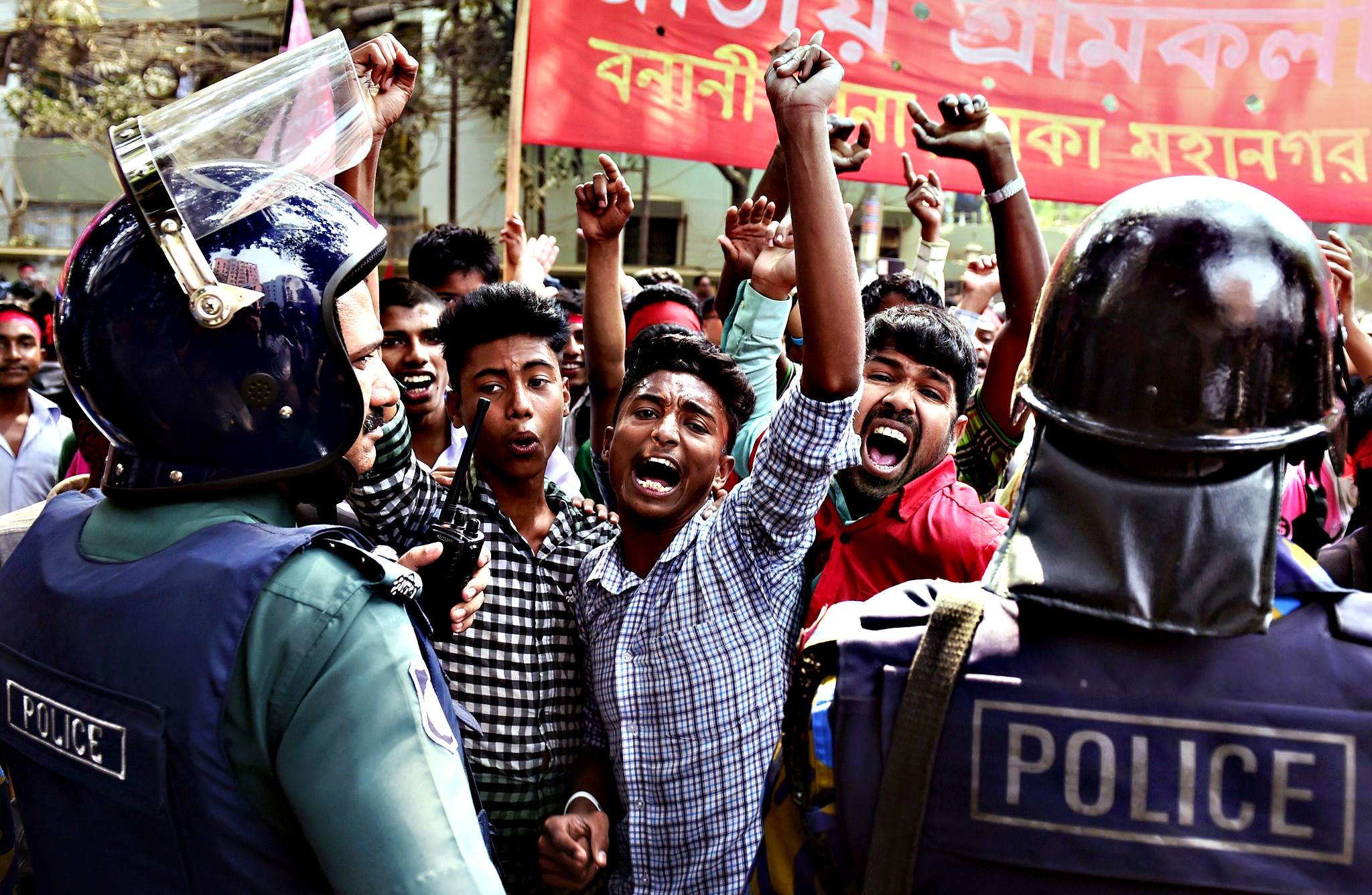 Bangladesh police stop activists from the Road Transport League, a wing of the ruling Bangladesh Awami League as they protest against the on-going nationwide strike outside the Bangladesh Nationalist Party office in Dhaka on February 9, 2015.  Violence triggered by the nationwide strike and blockade of roads, railways and waterways has reportedly left 80 people dead