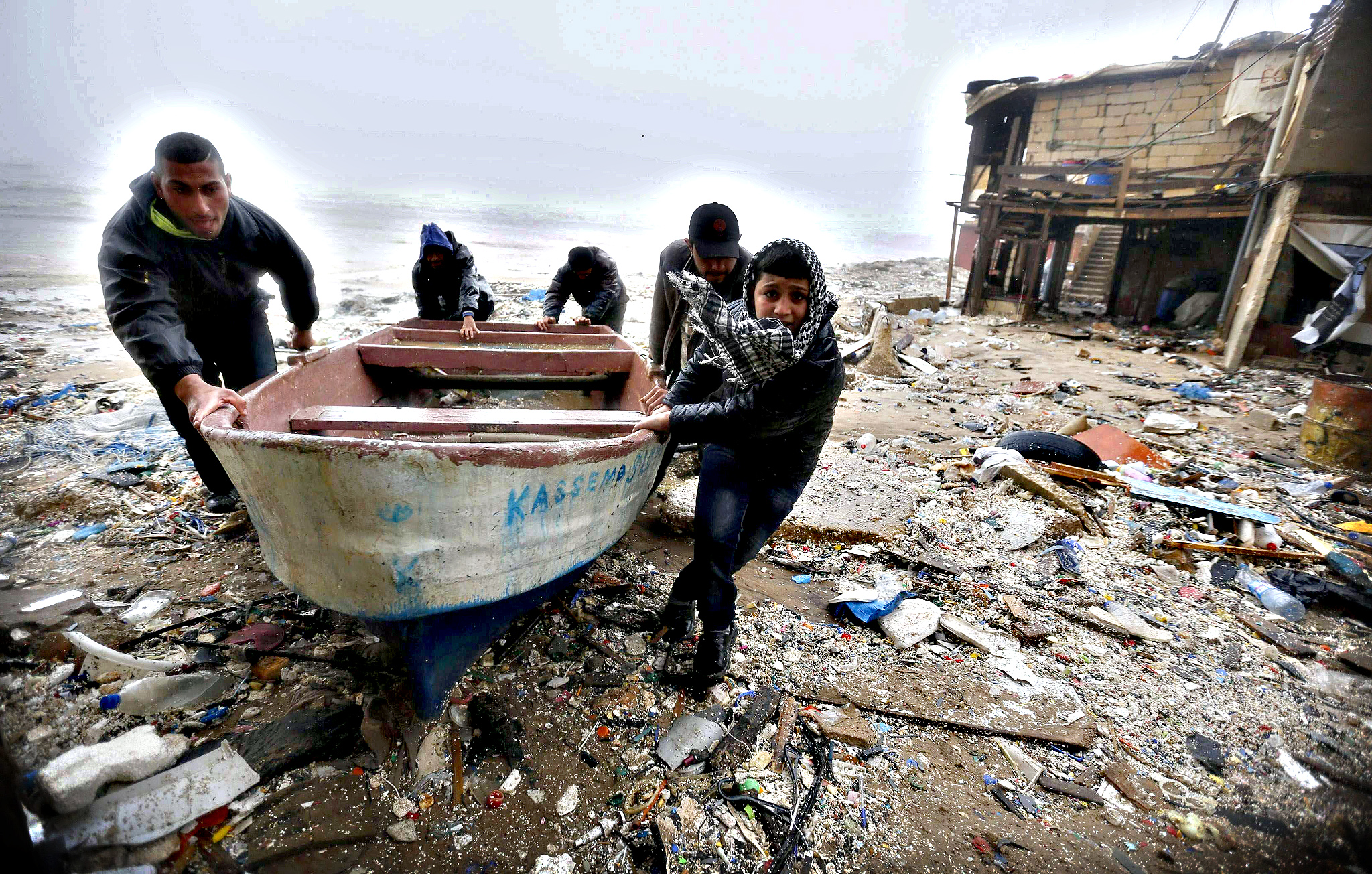 Fishermen move a boat that had been blown inland during a storm, by the seaside in Beirut on Wednesday