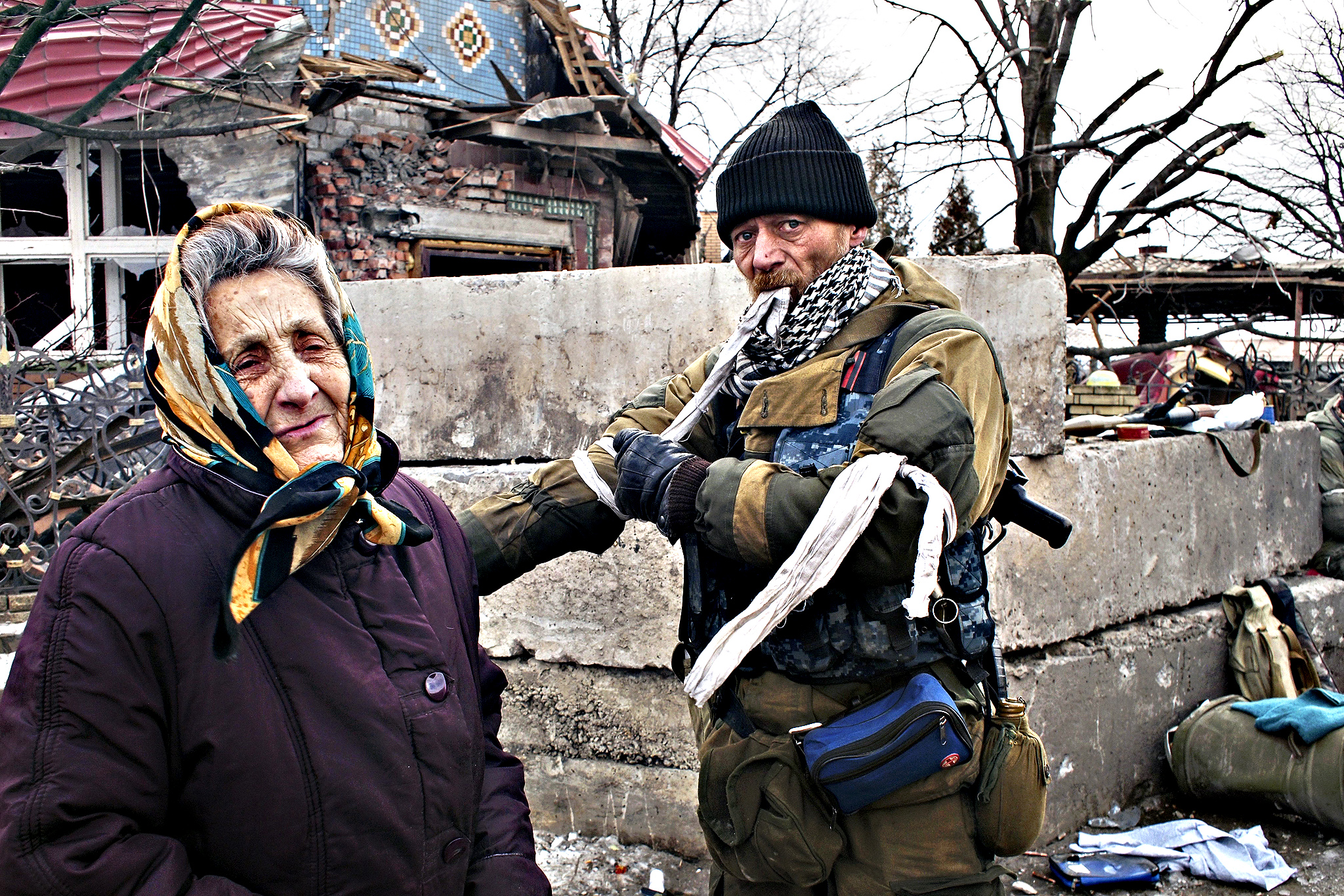 A pro-Russian rebel takes a ribbon from his arm in Debaltseve, eastern Ukraine on Thursday, Feb. 19, 2015. The ribbons are used as a form of identification. After weeks of relentless fighting, the embattled Ukrainian rail hub of Debaltseve fell Wednesday to Russia-backed separatists, who hoisted a flag in triumph over the town. The Ukrainian president confirmed that he had ordered troops to pull out and the rebels reported taking hundreds of soldiers captive.