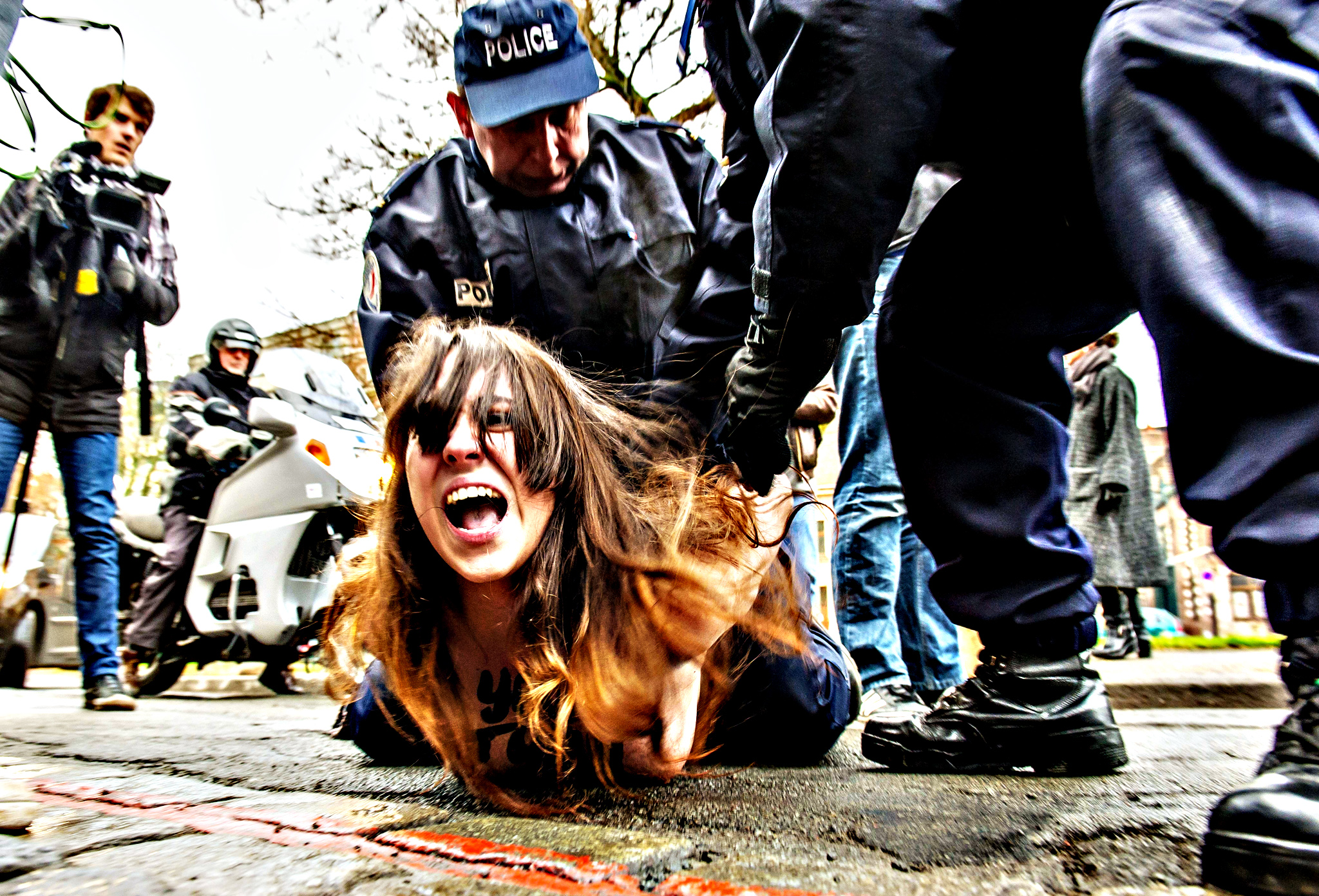 """Policemen detain a topless Femen activist after she jumped in front of the car carrying former IMF chief Dominique Strauss-Kahn (not seen) upon his arrival for his trial in Lille, northern France, on February 10, 2015. Three topless women from the protest group Femen jumped on the car of Dominique Strauss-Kahn as the former IMF chief arrived to testify at his trial for """"aggravated pimping."""" With slogans scrawled on their half-naked bodies and hurling insults at the car, the three protesters were quickly rounded up by police as the car entered an underground parking area."""