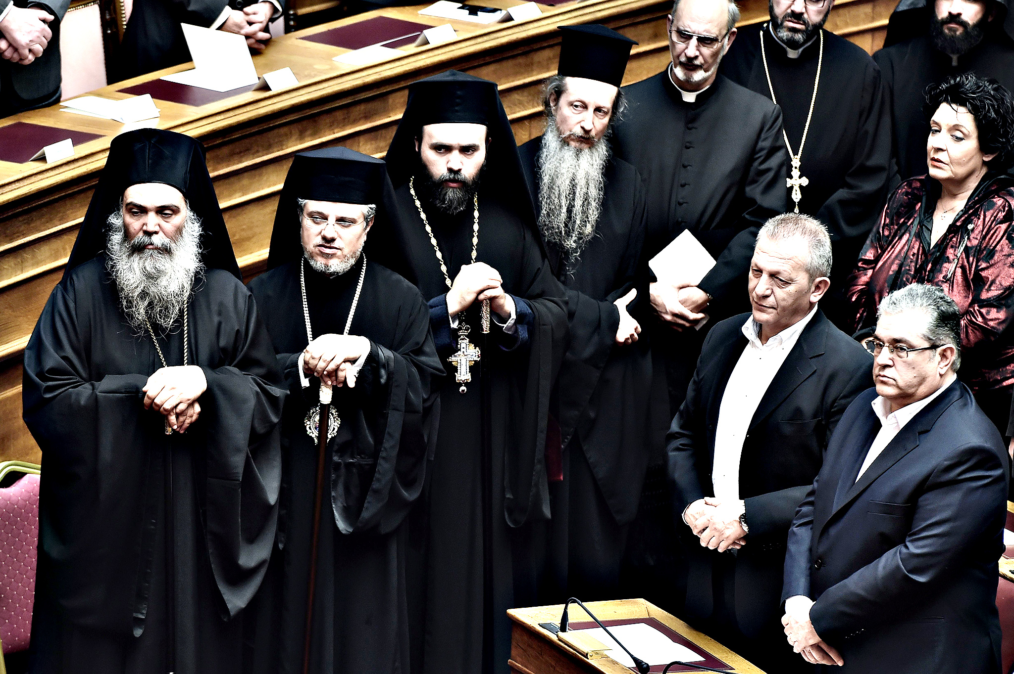 Dimitris Koutsoumpas (R), general secretary of the Communist Party of Greece (KKE) and religious officials attend a swearing in ceremony of the new parliament in Athens on February 5, 2015. Greece's parliament met for the first time after last month's election amid market jitters sparked by an ECB block on a key source of funding for Athens' banks.