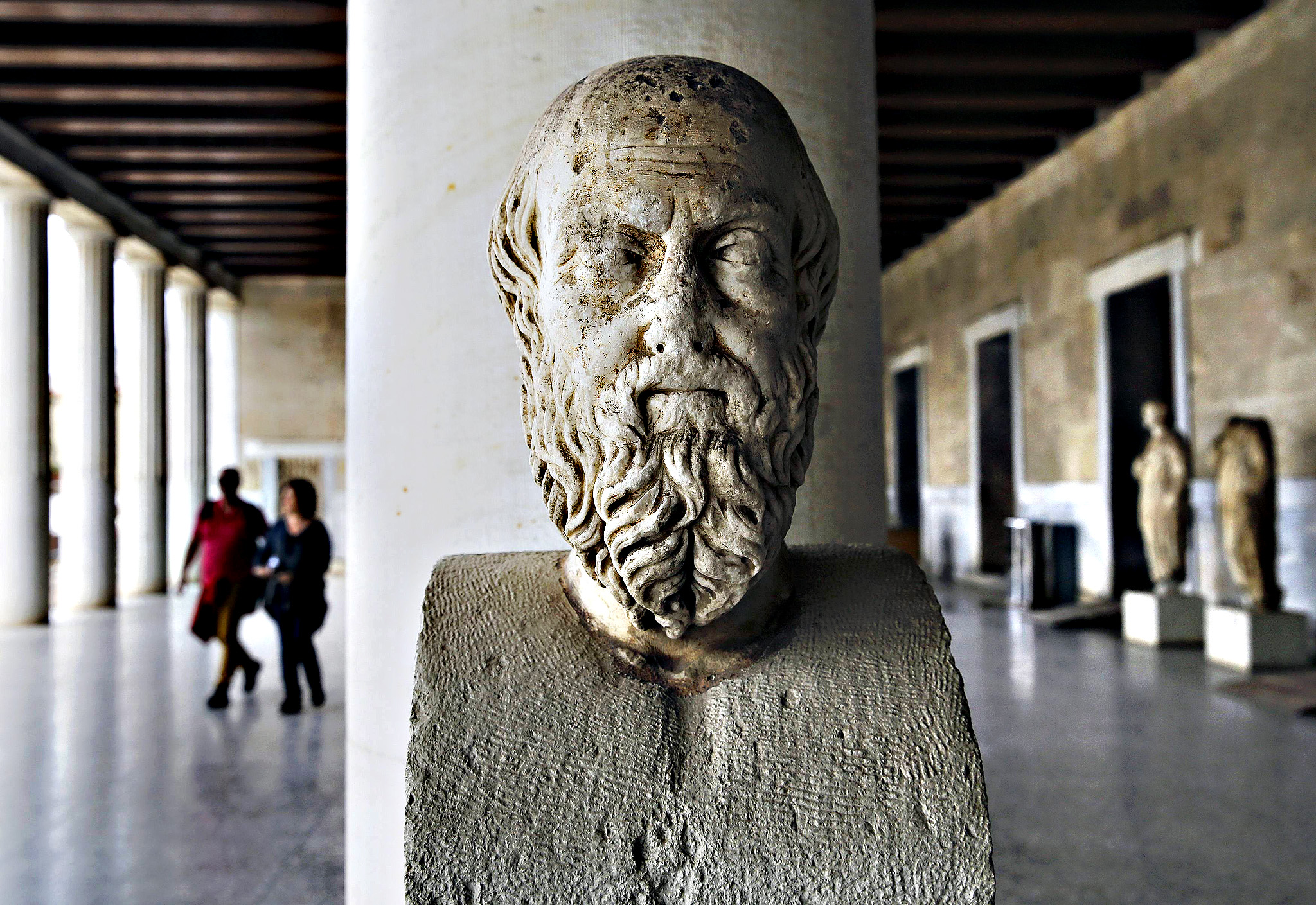 Tourists visit the Attalos arcade in Athens...An ancient marble head of Greek historian Herodotus is seen as tourists walk through the Attalos arcade in Athens February 26, 2015.  Greece's economy is expected to grow this year but faces risks from the government's ability to fulfill a deal with the euro zone and reform fatigue, central bank governor Yannis Stournaras said in his annual report published on Thursday. The arcade was erected by Attalos II King of Pergamon 159-138 BC and the building was reconstructed by the American school of classical studies in Athens under the authority of the Greek Ministry of Education in the reign of King Paul in 1953-1956.