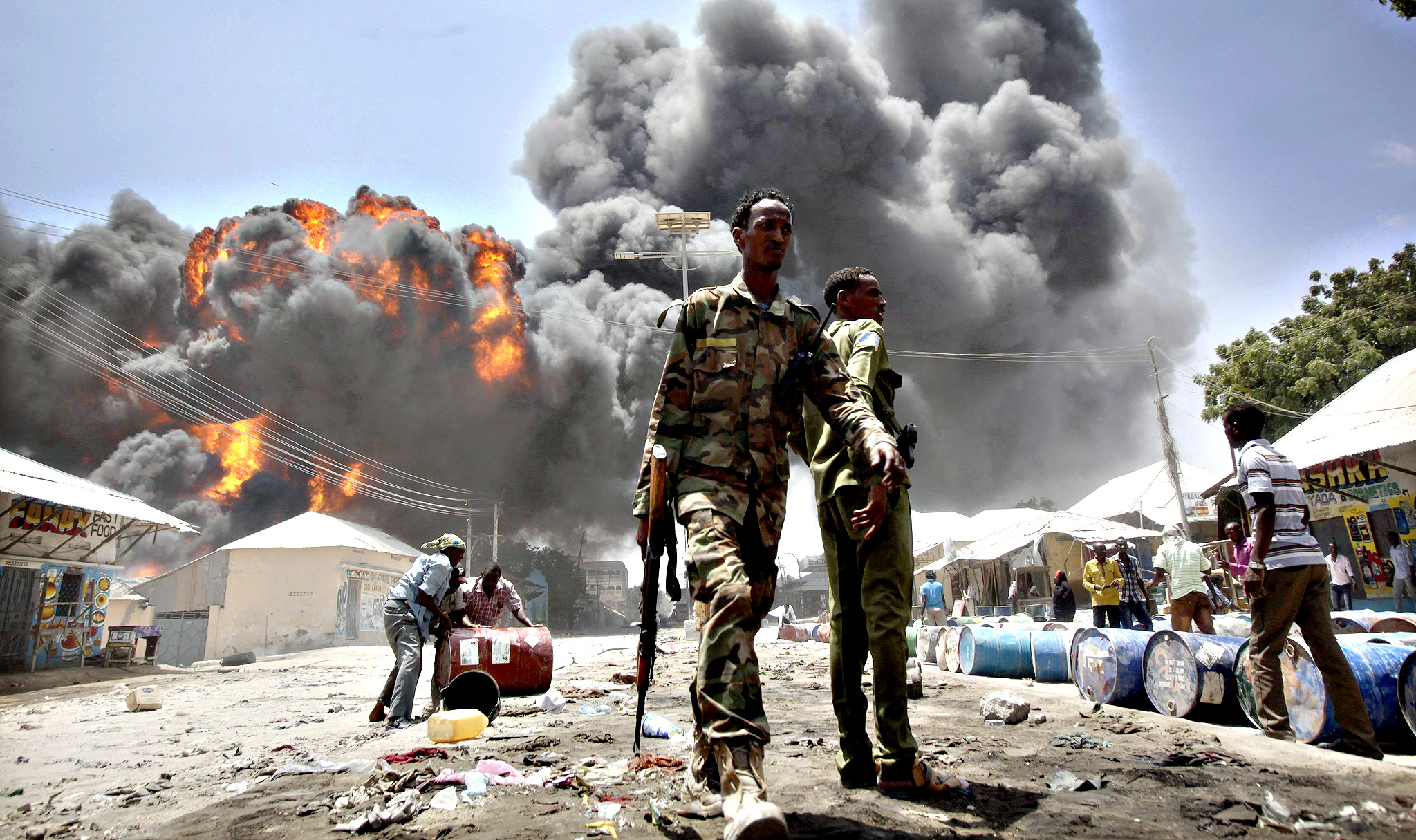 Soldiers watch as people move oil barrels away from the site of an explosion at a petrol station and storage facility near the Bakara open-air market in Mogadishu...Soldiers watch as people move oil barrels away from the site of an explosion at a petrol station and storage facility near the Bakara open-air market in Somalia's capital Mogadishu, February 23, 2015.