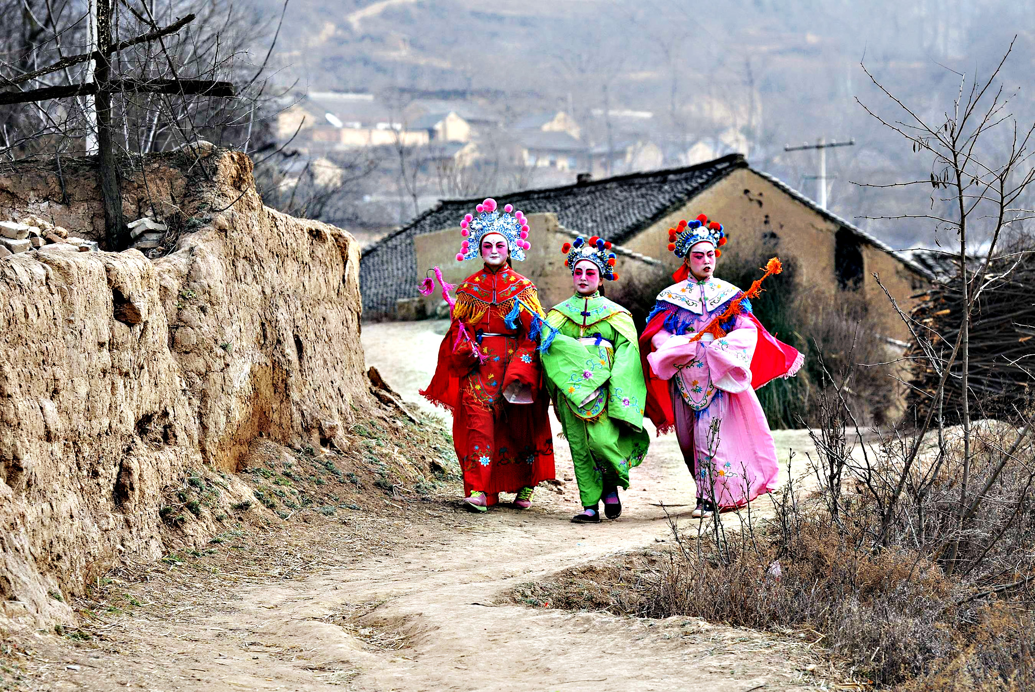 Girls dressed in traditional costumes and holding props walk before a performance in Longxian county, Shaanxi province. The children and villagers wore make-up and traditional costumes as they paraded around the village as part of the Chinese Lunar New Year celebration
