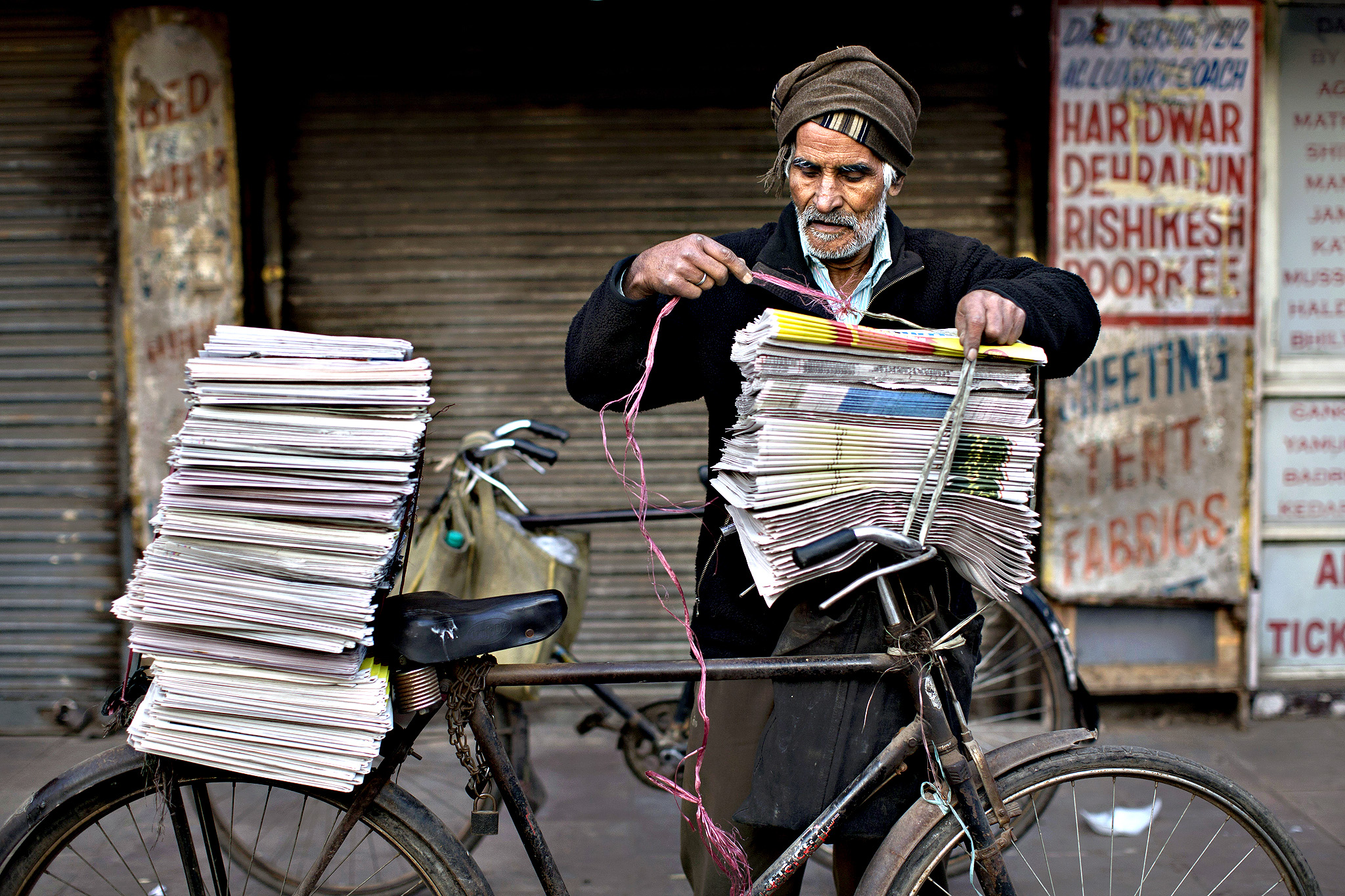 An Indian newspaper vendor ties newspapers on his bicycle early in the morning at the old city area of New Delhi, India, Friday, Feb. 27, 2015. Old Delhi despite of being extremely crowded and dilapidated still serves as the symbolic heart of the city.
