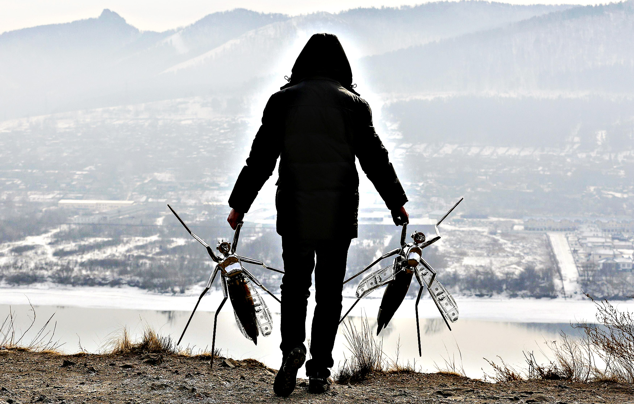 "Russian artist Vasily Slonov carries props he called ""Oil Mosquitoes"", which are made of stainless steel and glass filled with natural oil, for a demonstration of an installation on a bank of the Yenisei River in the Siberian city of Krasnoyarsk February 25, 2015. Slonov showed his installation called ""Mosquitoes exhausting the oil, the blood of the Earth"" ahead of the opening the Krasnoyarsk Economic Forum on February 26."
