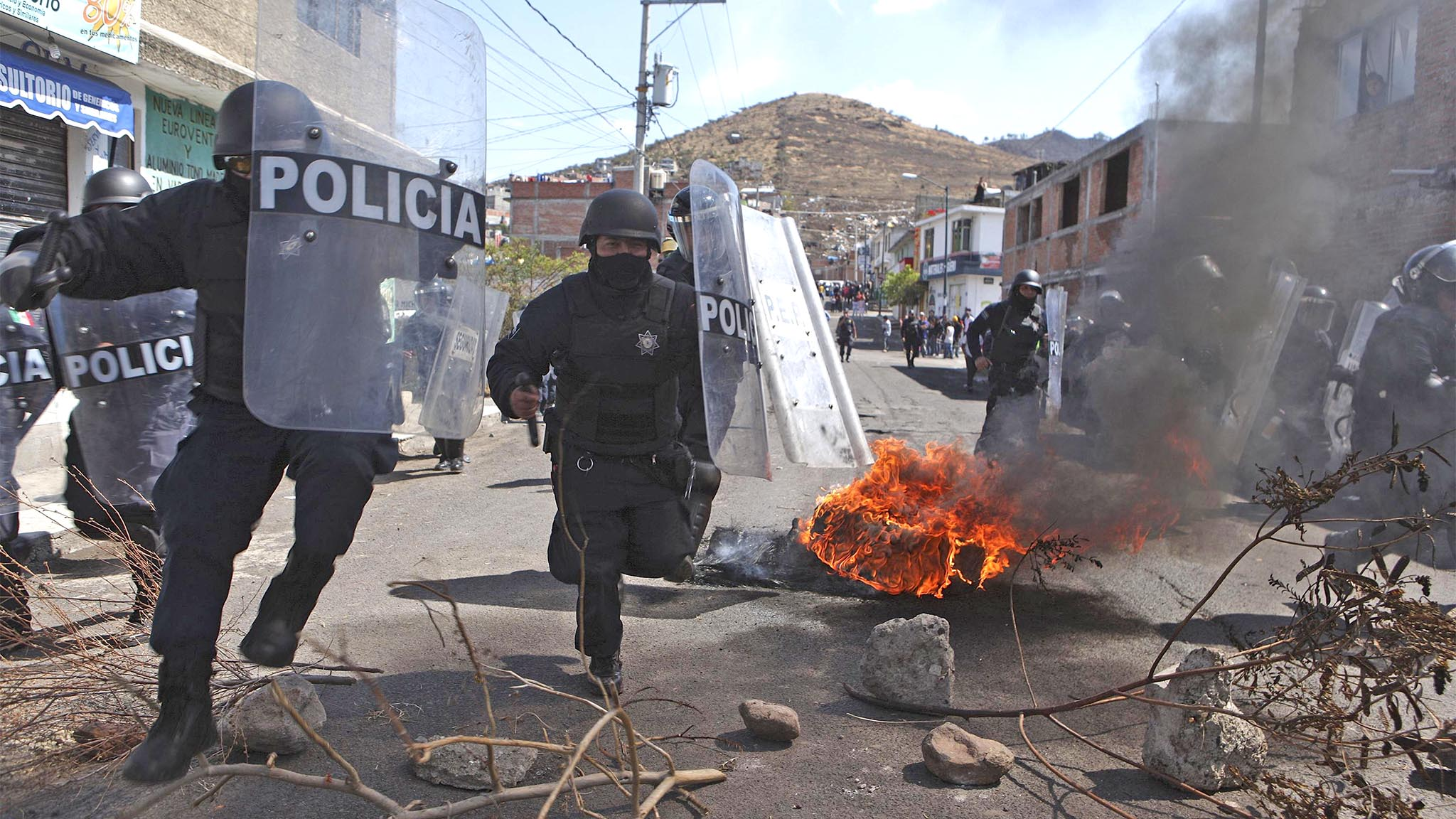 Riot policemen charge at squatters, who were throwing rocks at them, during an eviction at a squatter settlement in Morelia