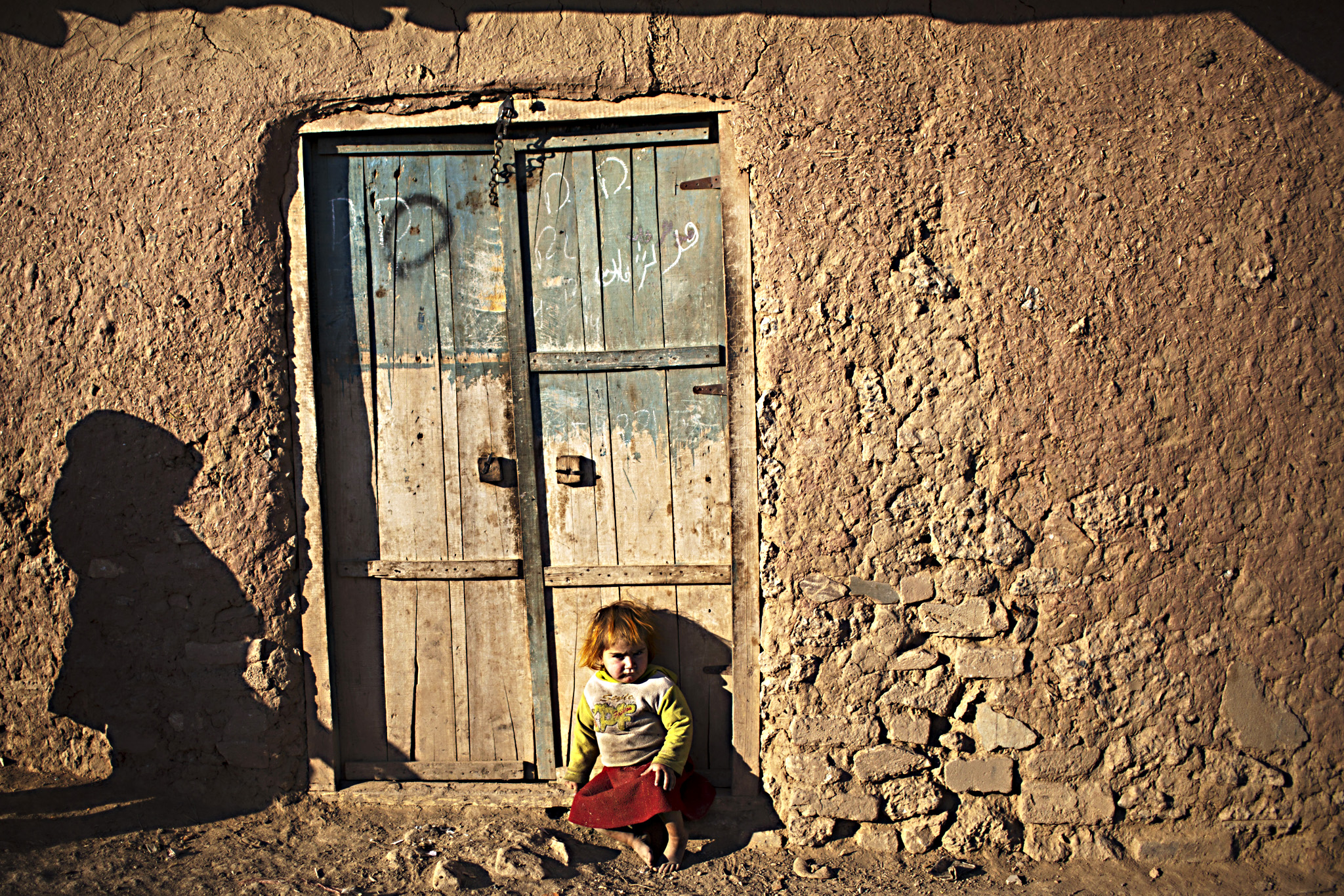 An Afghan refugee child sits at the doorway of a mud home in a slum on the outskirts of Islamabad, Pakistan, Monday, Feb. 9, 2015.