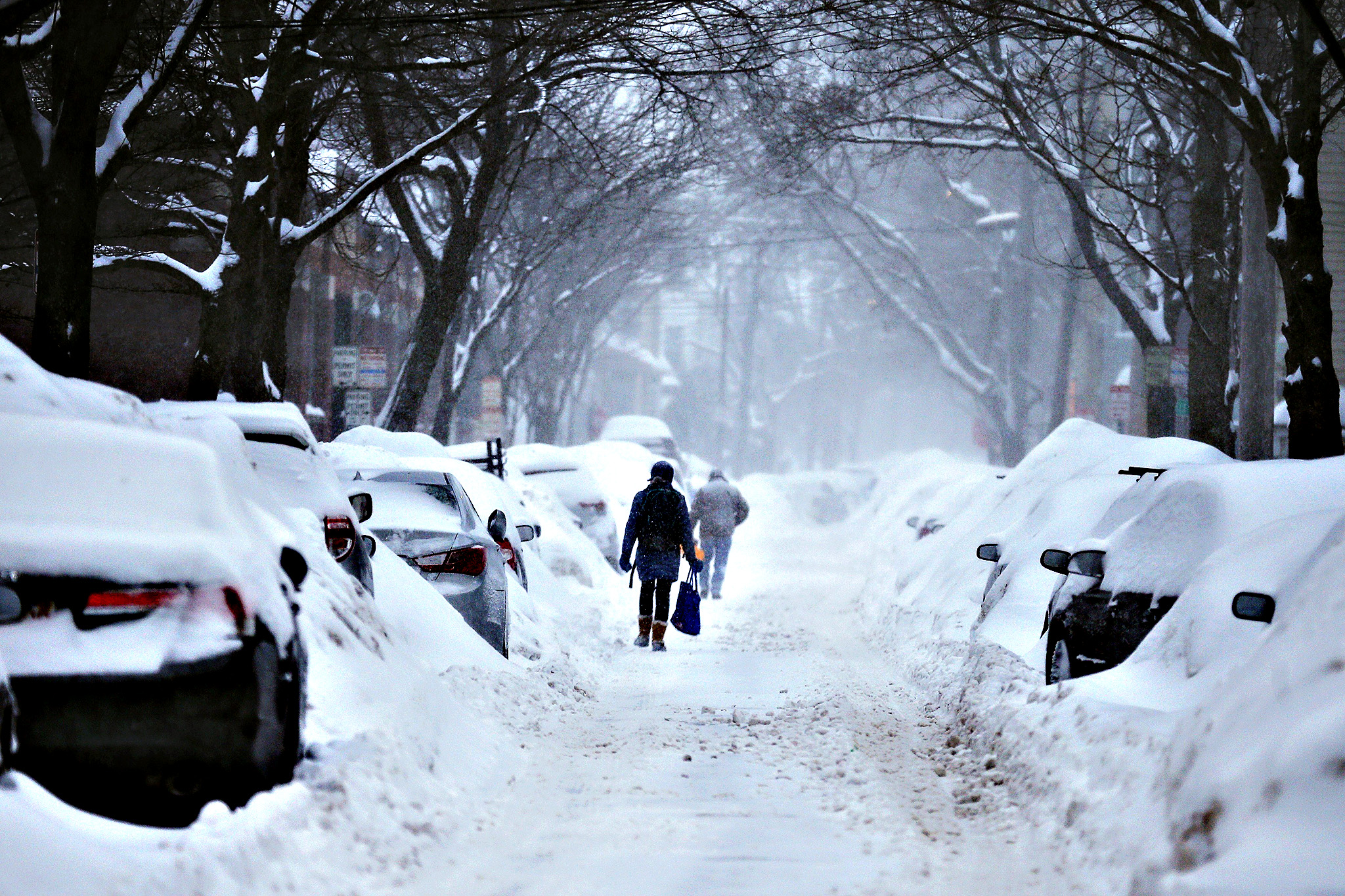 Pedestrians make their way along a snow covered street during a winter snow storm in Cambridge, Massachusetts February 9, 2015.  Boston and other areas of the Northeast, already buried under about a yard of snow, braced for up to two more feet through early Tuesday while more rain and high winds were in store for parts of the Pacific coast, forecasters said on Sunday