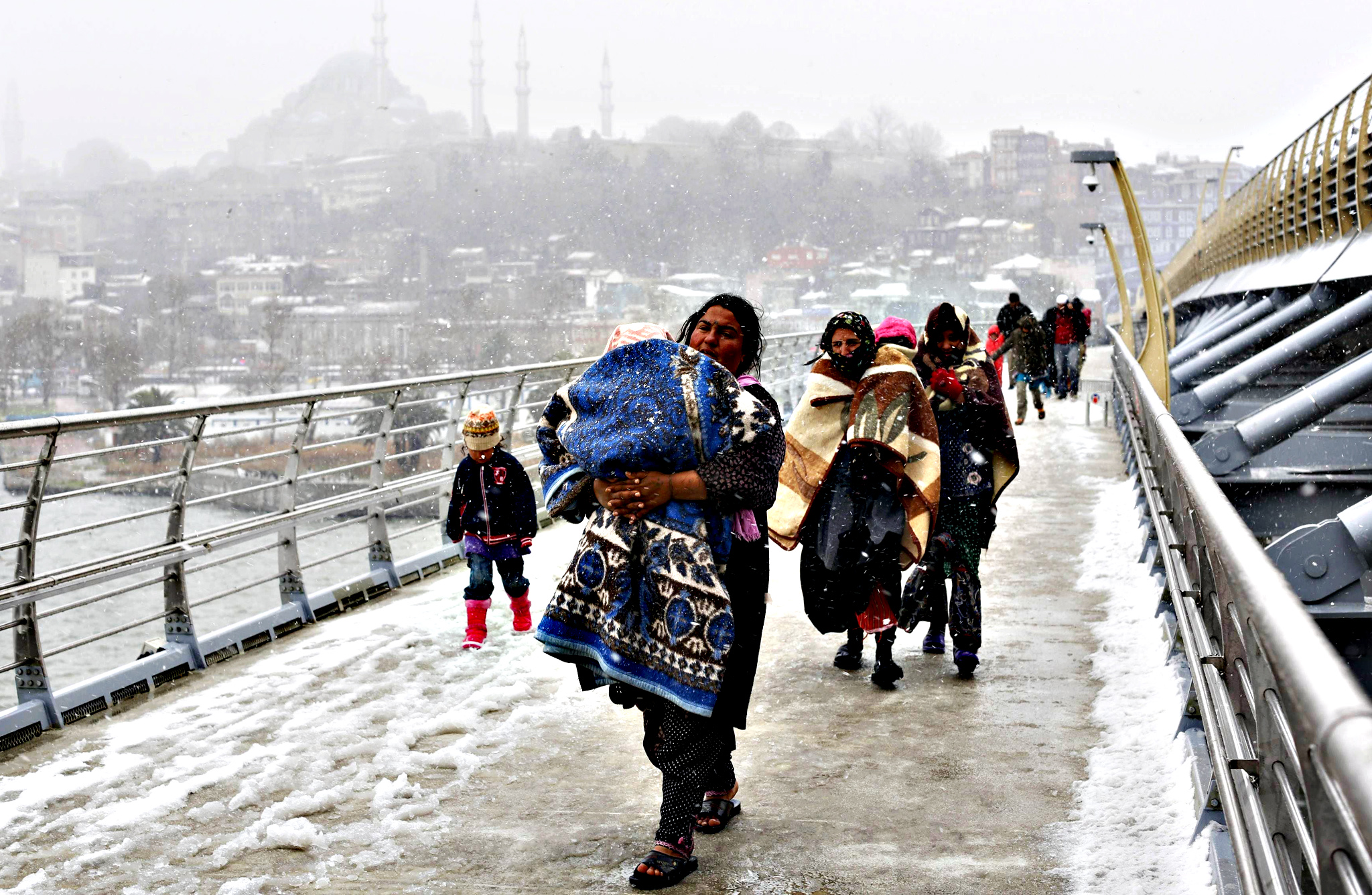 Syrian refugees brave the cold and snow as they walk to a metro station in Istanbul February 11, 2015, at the start of a day's begging. The civil war, which began as a popular uprising against President Bashar al-Assad in March 2011, has killed 200,000 people and turned 3 million more into refugees. At least 3.7 million people have fled Syria's almost four-year conflict and are registered as refugees, mainly in neighbouring states. Jordan hosts 622,000 Syrian refugees, Lebanon 1.16 million, Turkey 1.6 million and Iraq 233,000, UNHCR figures show.