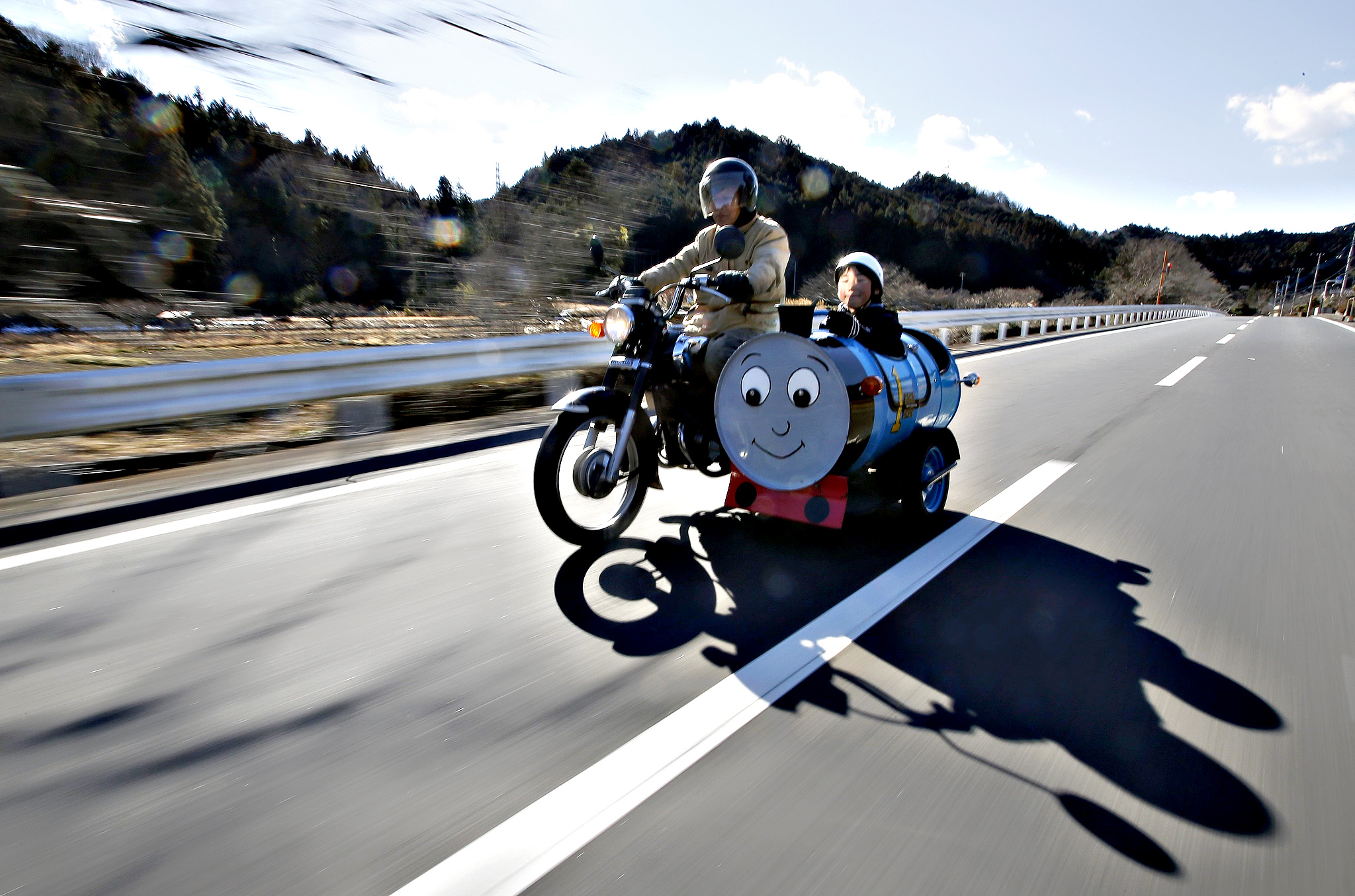 Sadao Kimbara rides on a Honda motorcycle with a sidecar he made out of an oil barrel as his grandson Rui smiles in the sidecar in Ome, outskirts of Tokyo...Sadao Kimbara (L) rides on a Honda motorcycle with a sidecar he made out of an oil barrel as his grandson Rui smiles in the sidecar in Ome, outskirts of Tokyo February 14, 2015. Saudi Arabia's oil exports have risen in February in response to stronger demand from customers. As OPEC's top producer battles for market share Reuters photographers around the globe have been photographing oil barrels to document how they are utilised once the fuel has been used.