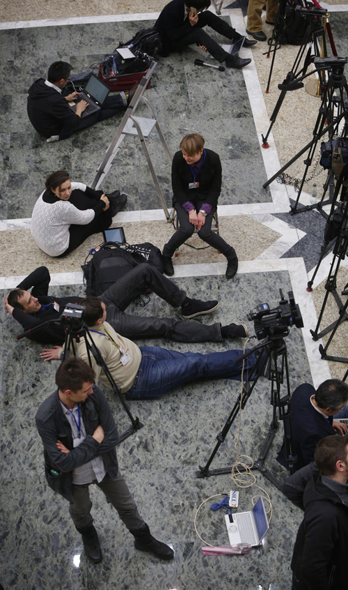 Journalists wait outside the meeting room in Minsk, Belarus as Ukrainian peace talks dragged on deep into a second day Thursday,