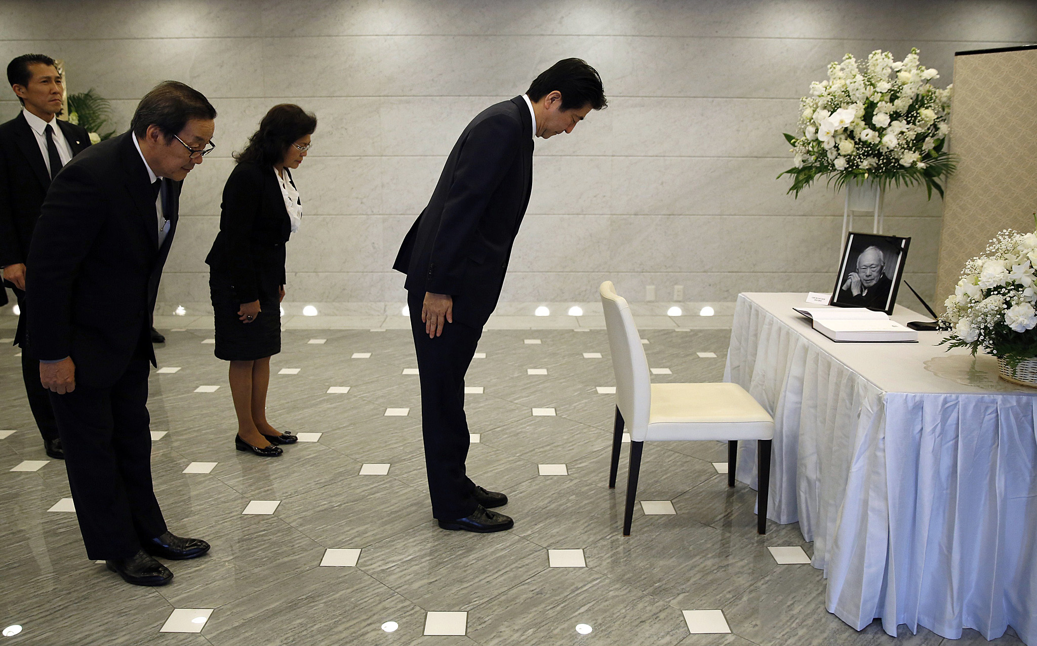 Japan's Prime Minister Shinzo Abe (R) bo...Japan's Prime Minister Shinzo Abe (R) bows with Singapore Ambassador to Japan Chin Siat Yoon (front L) and his wife Wang Lee Moi (3rd R) after signing a condolence book for the late former Singapore prime minister Lee Kuan Yew at the Singapore Embassy in Tokyo on March 24, 2015. Singapore's first prime minister Lee Kuan Yew, one of the towering figures of post-colonial Asian politics, died at the age of 91 on March 23.     AFP PHOTO / POOL / Toru HanaiTORU HANAI/AFP/Getty Images