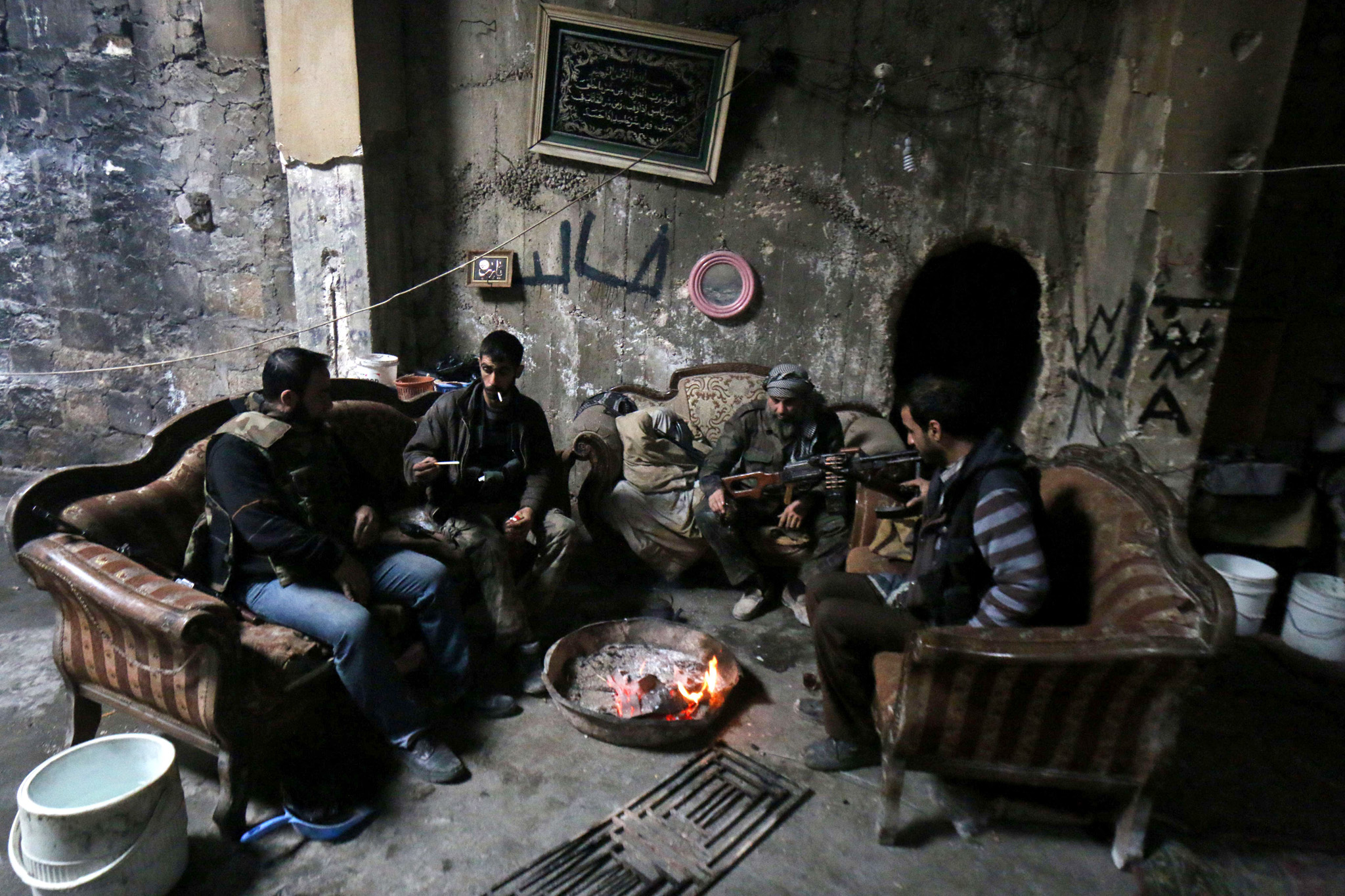 Opposition fighters sit inside a damaged...Opposition fighters sit inside a damaged building in the rebel-held Qastal al-Harami neighborhood, in the northern Syrian city of Aleppo, on March 24, 2015. AFP PHOTO / AMC / ZEIN AL-RIFAIZEIN AL-RIFAI/AFP/Getty Images