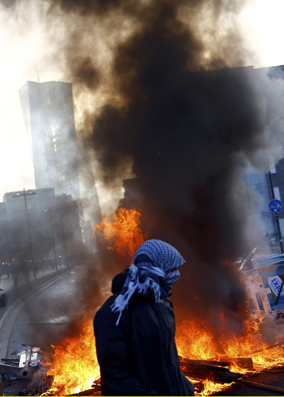 A 'Blockupy' anti-capitalist protester walks near a burning barricade near the European Central Bank (ECB) building before the official opening of its new headquarters in Frankfur