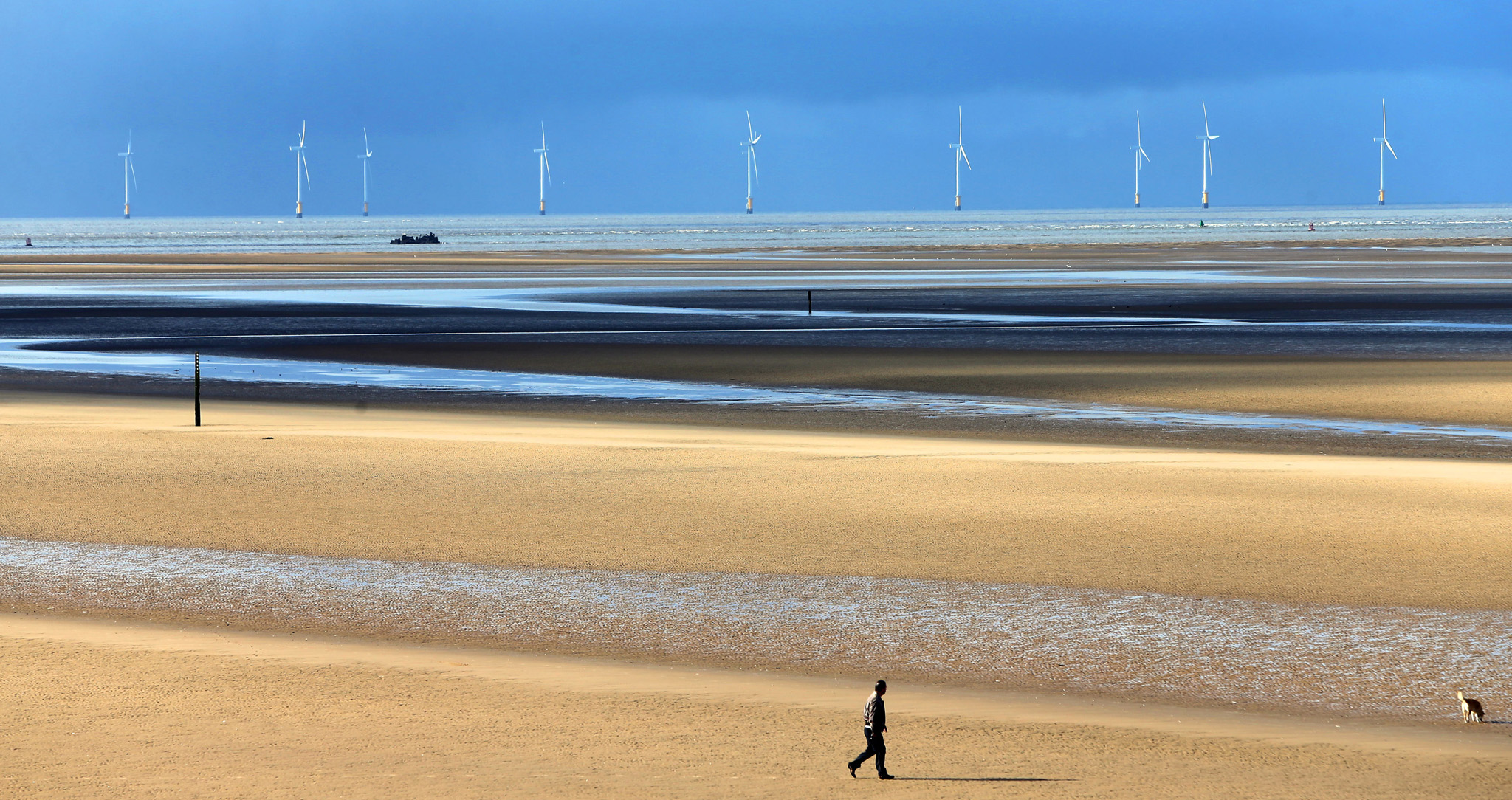 Spring weather March 24th 2015...A man walks his dog along Formby Beach, Merseyside, as a shipwreck can be seen in the distance. PRESS ASSOCIATION Photo. Picture date: Tuesday March 24, 2015. Photo credit should read: Peter Byrne/PA Wire