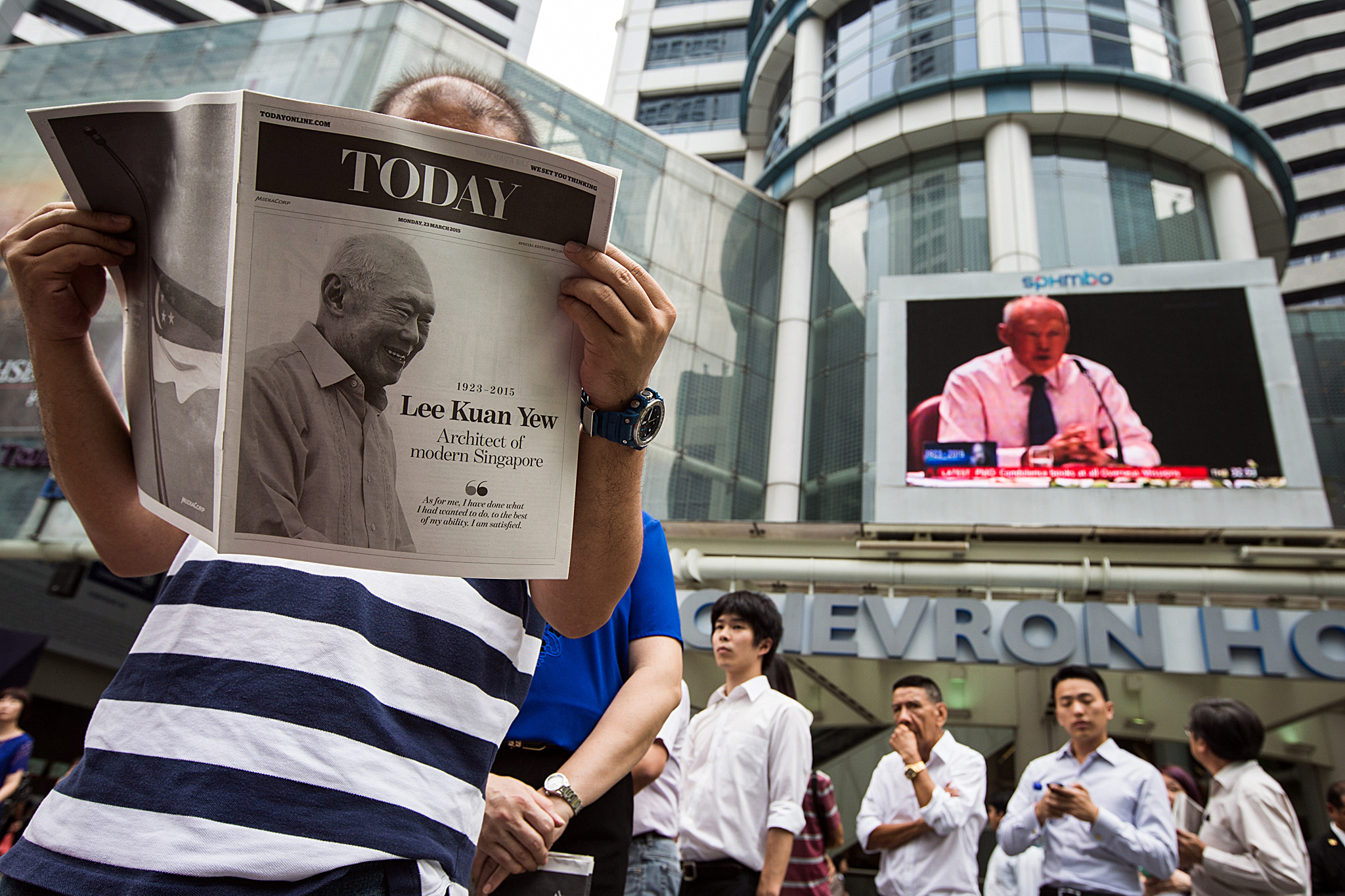 Reactions To The Death Of Singapore's Founding Prime Minister Lee Kuan Yew...A monitor shows coverage of the death of Singapore's first elected Prime Minister Lee Kuan Yew as a man reads a special edition of a Today newspaper, produced by MediaCorp Press Ltd., at Raffles Place in Singapore, on Monday, March 23, 2015. Lee, who helped transform Singapore from a colonial trading center into one of Asia's most prosperous nations, has died. He was 91. Photographer: Nicky Loh/Bloomberg