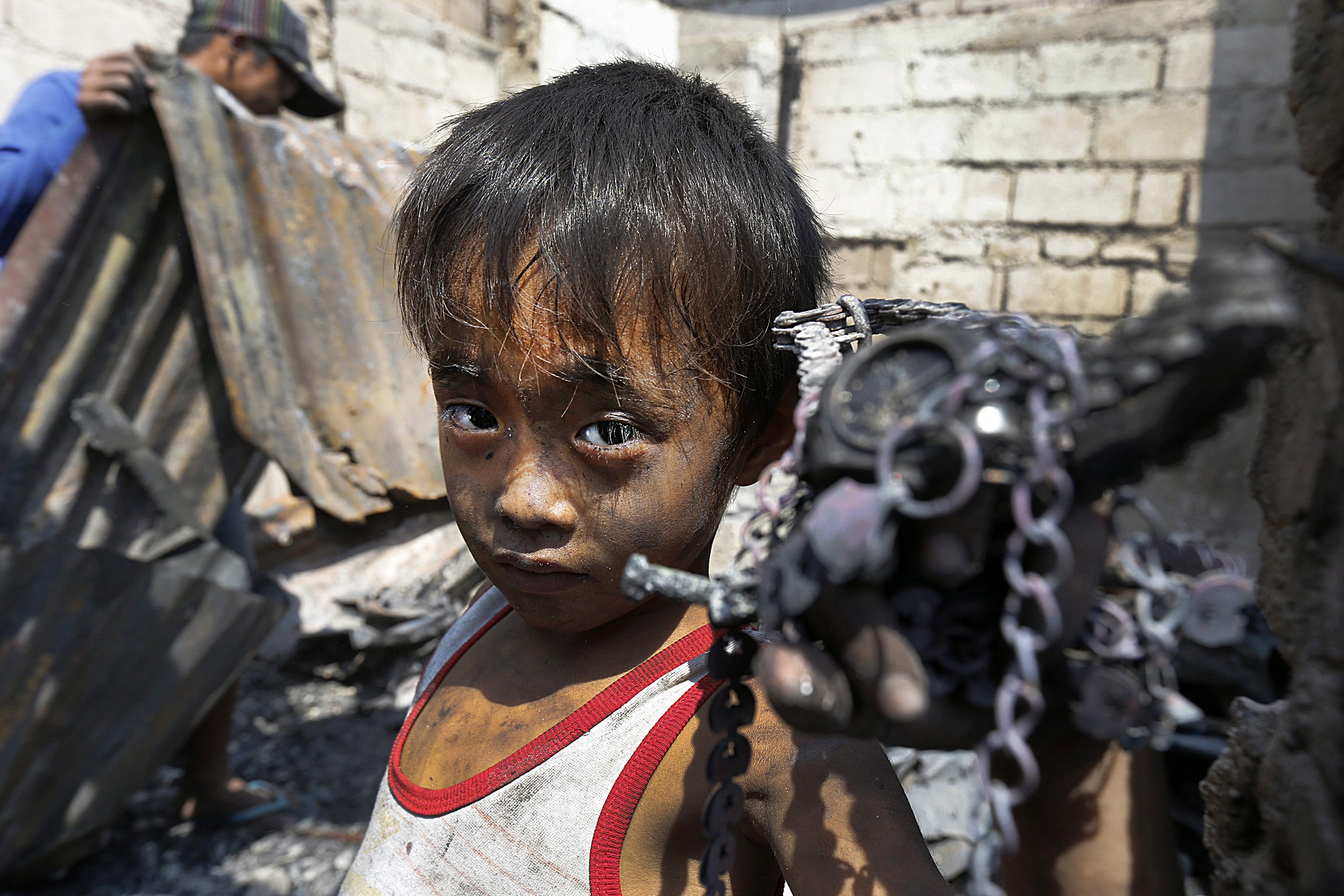 Fire razed 250 houses and killed two residents...epa04667151 Majay Bugarin,5, shows  materials  he collected among debris after a fire that razed a slum area in Malabon City, north of Manila, Philippines, 18 March 2015. According to arson investigators from the Bureau of Fire Protection (BFP), two residents were killed and  more than 500 families were rendered homeless by a blaze that swept through some 400 houses at a shanty town amid the start of the country's fire safety month. Fire Prevention Month is observed in the month of March, with incidents of fire expected to increase during summer.  EPA/DENNIS M. SABANGAN