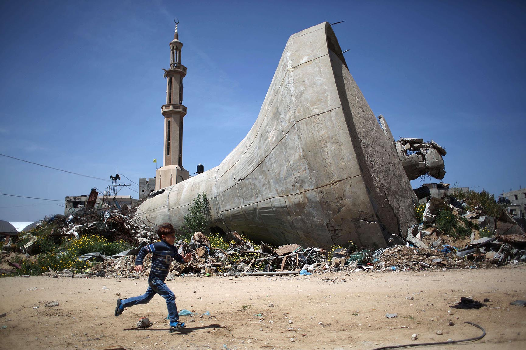 A Palestinian child runs past a water tank