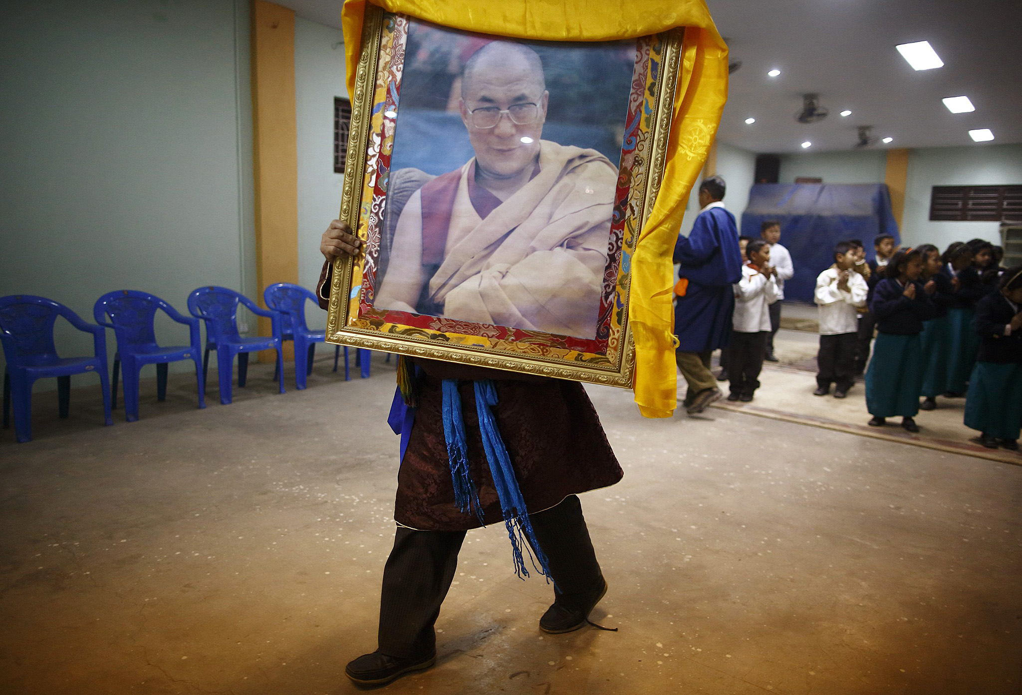A Tibetan man carries a portrait of exiled Tibetan spiritual leader, the Dalai Lama, during a function to mark the 56th Tibetan Uprising Day at the Tibetan Refugee camp in Lalitpur...A Tibetan man carries a portrait of exiled Tibetan spiritual leader, the Dalai Lama, during the function to mark the 56th Tibetan Uprising Day at the Tibetan Refugee camp in Lalitpur March 10, 2015. With a growing Chinese influence over Nepal, the Nepalese government stands strong against Tibetan exiles protesting in support of their homeland. Nepal ceased issuing refugee papers to Tibetans in 1989 and recognizes Tibet to be a part of China. REUTERS/Navesh Chitrakar (NEPAL - Tags: RELIGION POLITICS)