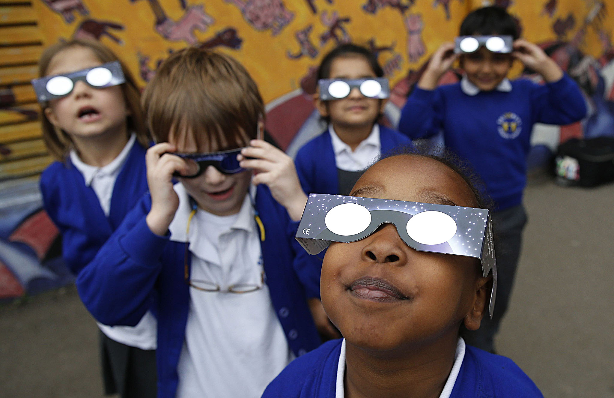 Children at a school wear solar viewing glasses as they try to see a partial solar eclipse in London...Children at a school wear solar viewing glasses as they try to see a partial solar eclipse in London March 20, 2015. A solar eclipse swept across the Atlantic Ocean on Friday with the moon blocking out the sun for a few thousand sky gazers on remote islands with millions more in Europe, Africa and Asia getting a partial celestial show. REUTERS/Suzanne Plunkett
