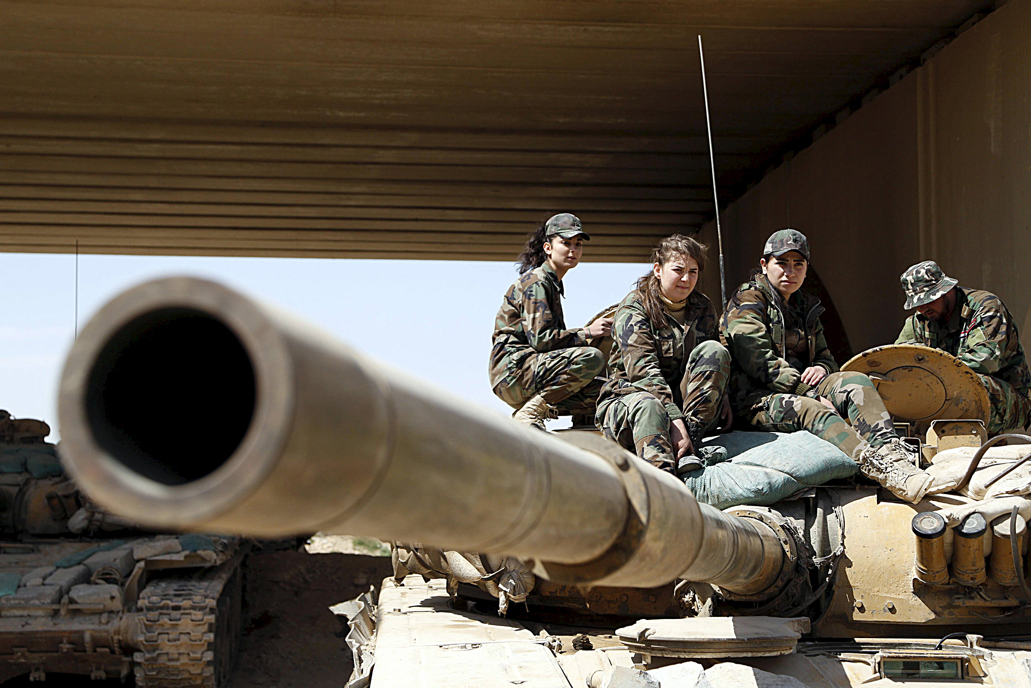 Members of a Female Commando Battalion which is part of the Syrian Army, sit atop of a tank in the government-controlled area of Jobar...Members of a Female Commando Battalion which is part of the Syrian Army, sit atop of a tank in the government-controlled area of Jobar, a suburb of Damascus March 19, 2015. This Battalion consists of several hundred female fighters who have had military training and carry out combat duties. Picture taken during a Syrian Army organised trip. REUTERS/Omar Sanadiki
