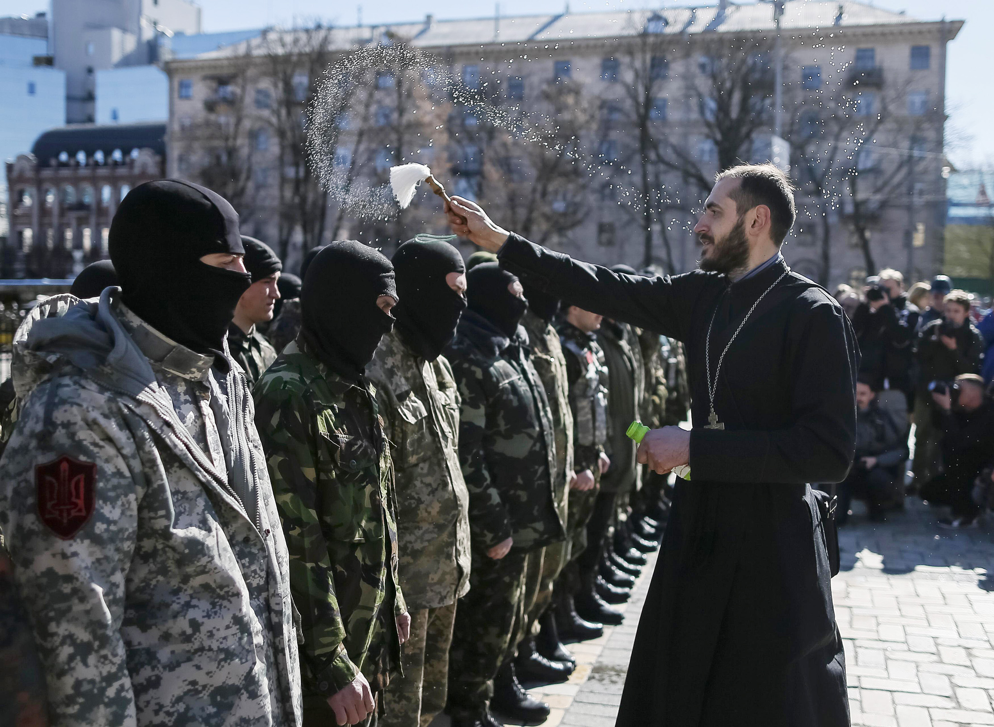 A priest sprinkles holy water on members of the Organization of Ukrainian Nationalists (OUN) before they depart to the frontline in eastern Ukraine, in central Kiev...A priest sprinkles holy water on members of the Organization of Ukrainian Nationalists (OUN) before they depart to the frontline in eastern Ukraine, in central Kiev, March 17, 2015. Three Ukrainian servicemen have been killed in fighting in the east of Ukraine in the past 24 hours despite a ceasefire agreement with Russian-backed rebels, a Kiev military spokesman said on Tuesday.  REUTERS/Gleb Garanich  (UKRAINE - Tags: POLITICS CIVIL UNREST CONFLICT RELIGION)