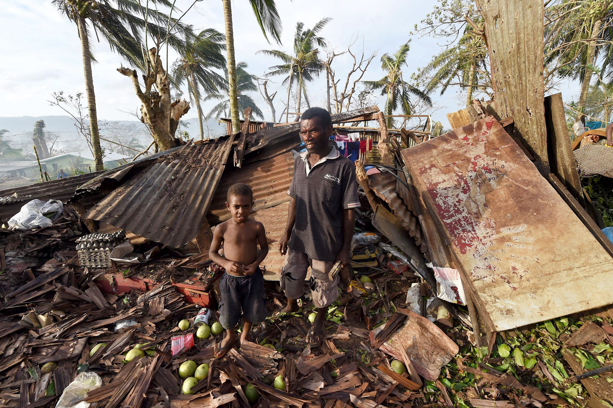 Cyclone Pam toll expected to rise...epa04664494 Samuel stands his father Phillip in what remained of their family home in Port Villa, capital of Vanuatu, 16 March  2015. International relief work was under way 16 March in Vanuatu and Tuvalu, impoverished island nations ravaged by the worst tropical cyclone on record in the South Pacific with aid agencies saying conditions in cyclone-ravaged Vanuatu are among the most challenging they have faced. Tropical Cyclone Pam left a trail of destruction when it ripped through the region at the start of the weekend with winds in excess of 250 kilometres per hour, heavy downpours and flooding.  EPA/DAVE HUNT AUSTRALIA AND NEW ZEALAND OUT