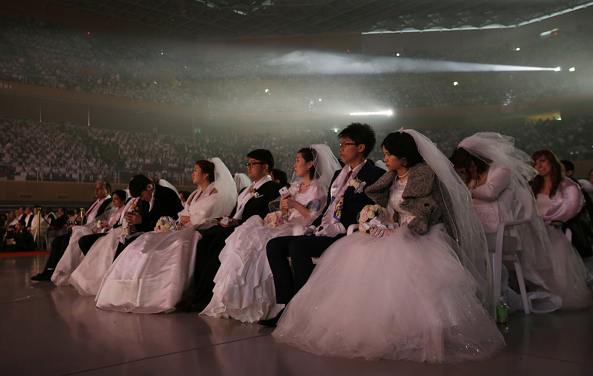 Couples from around the world watch a musical in a mass wedding ceremony at the Cheong Shim Peace World Center in Gapyeong, South Korea, Tuesday, March 3, 2015. 3,800 couples from more than fifty countries exchanged or reaffirmed marriage vows in the Unification Church's mass wedding arranged by Hak Ja Han Moon, wife of the late Rev. Sun Myung Moon, the controversial founder of the church. (AP Photo/Ahn Young-joon)