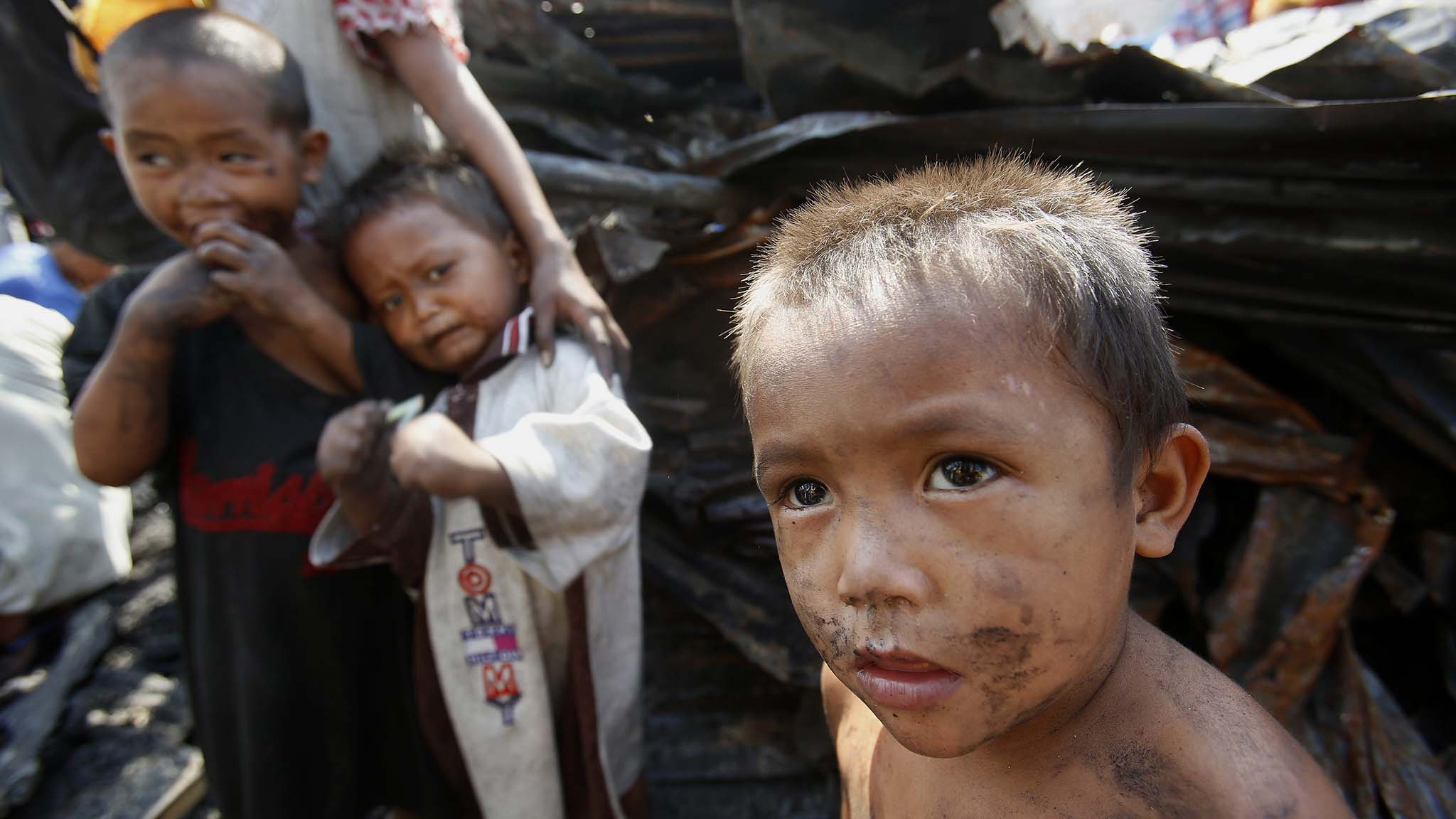 Children gather near their burnt home after a fire razed a squatters colony in Tondo, Manila