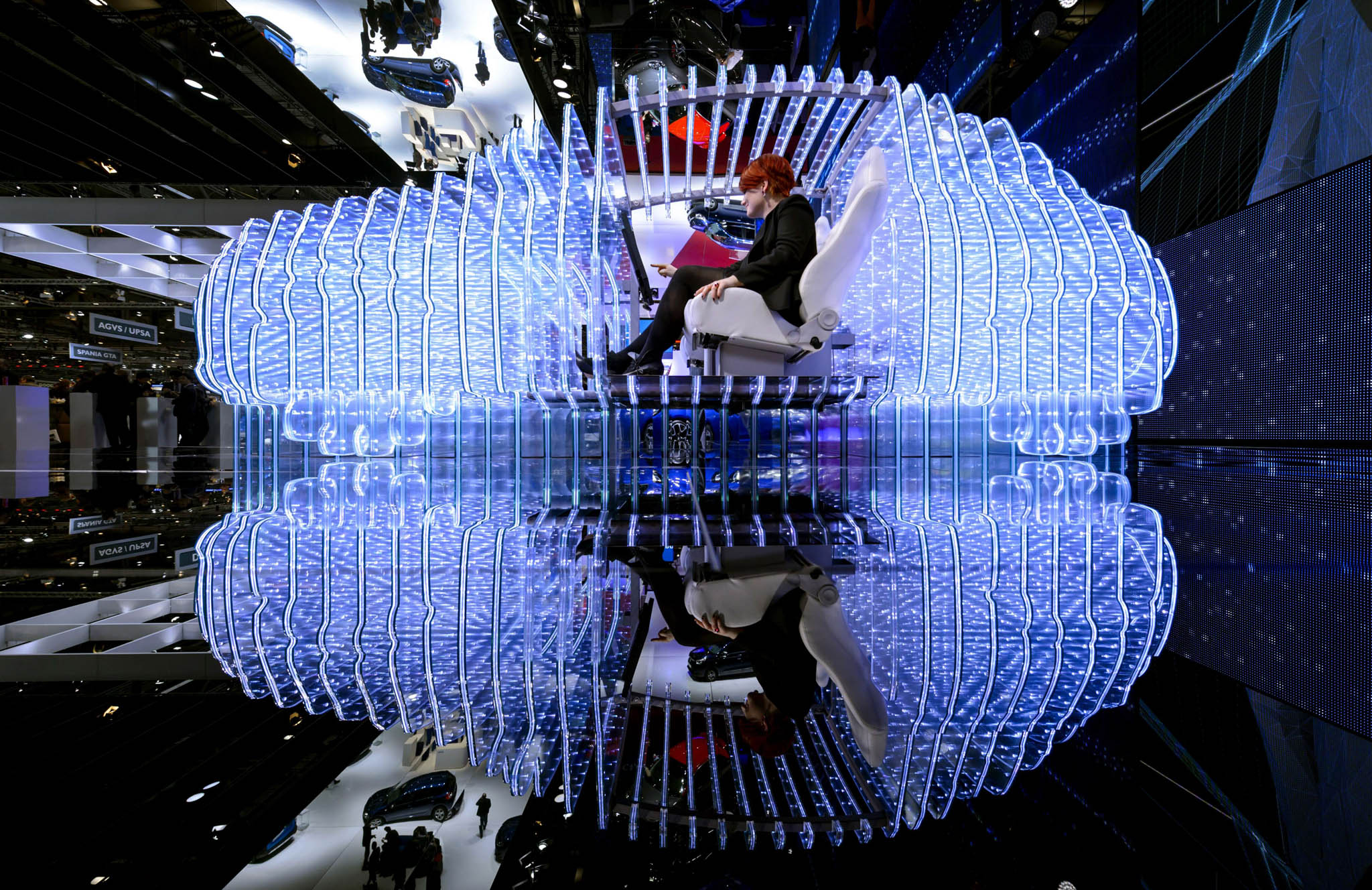 A woman poses inside the mockup of a car at the Opel booth during the press day of the Geneva Car Show