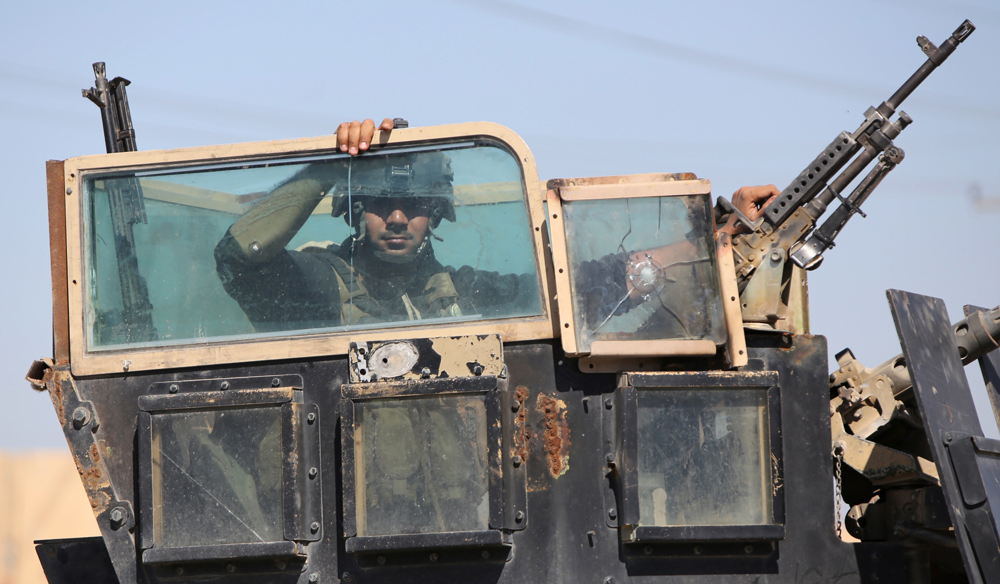 A member of the Iraqi government forces sits in an armed military vehicle on the outskirts of the northern city of Tikrit as they prepare to launch a military operation to take control of the city from Islamic State (IS) group fighters.