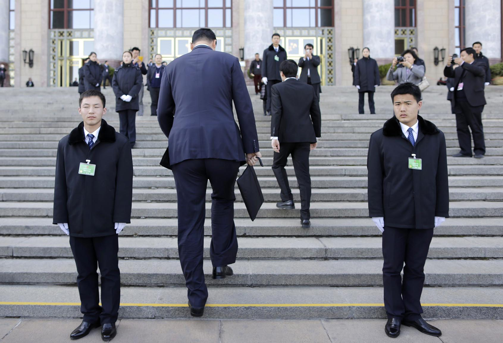 Former NBA basketball player Yao walks past security personnel as he arrives for the closing session of the CPPCC outside the Great Hall of the People, in Beijing