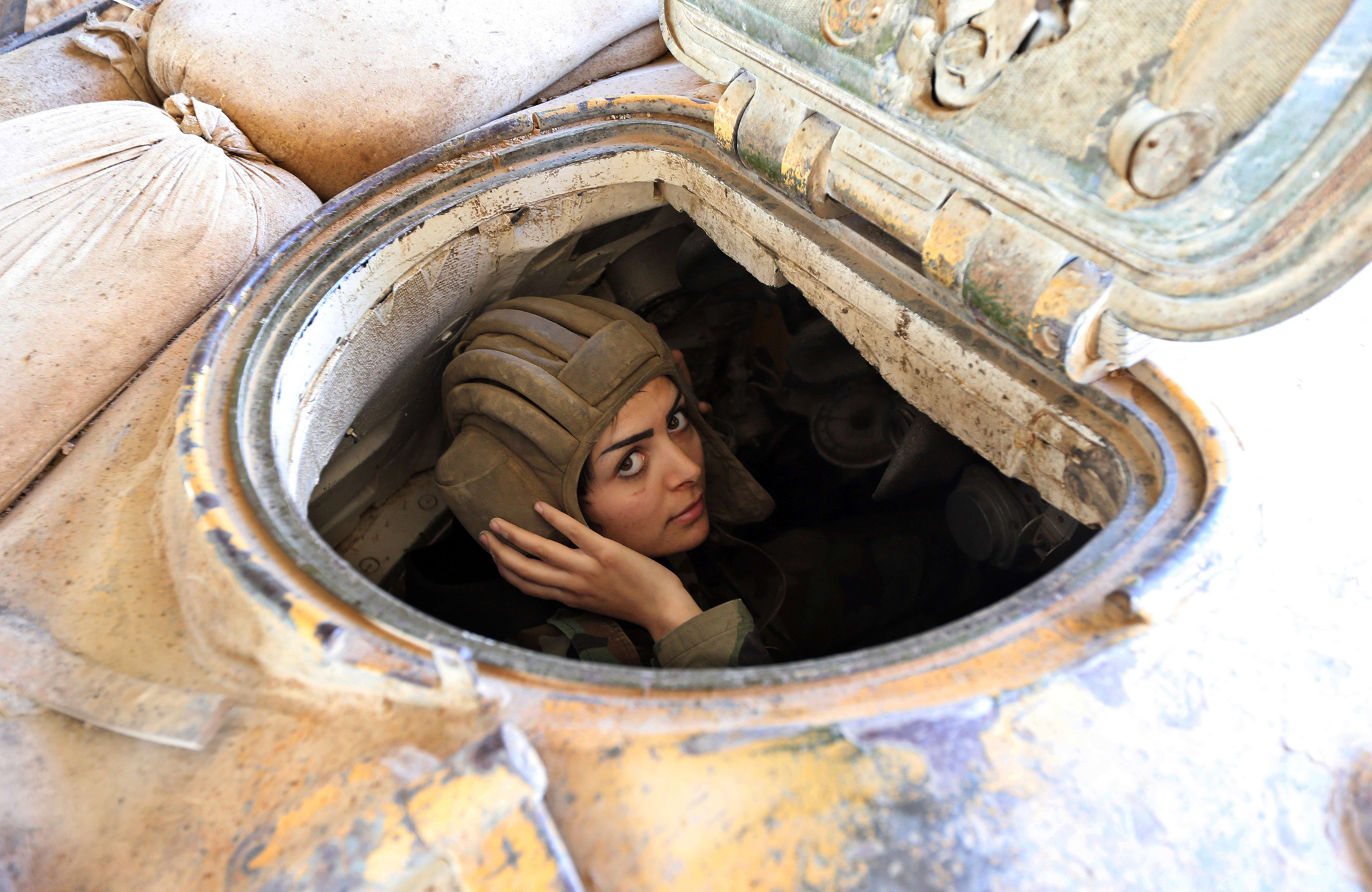 A female Syrian soldier from the Republican Guard commando battalion drives a tank during clashes with rebels in the restive Jobar area, in eastern Damascus.