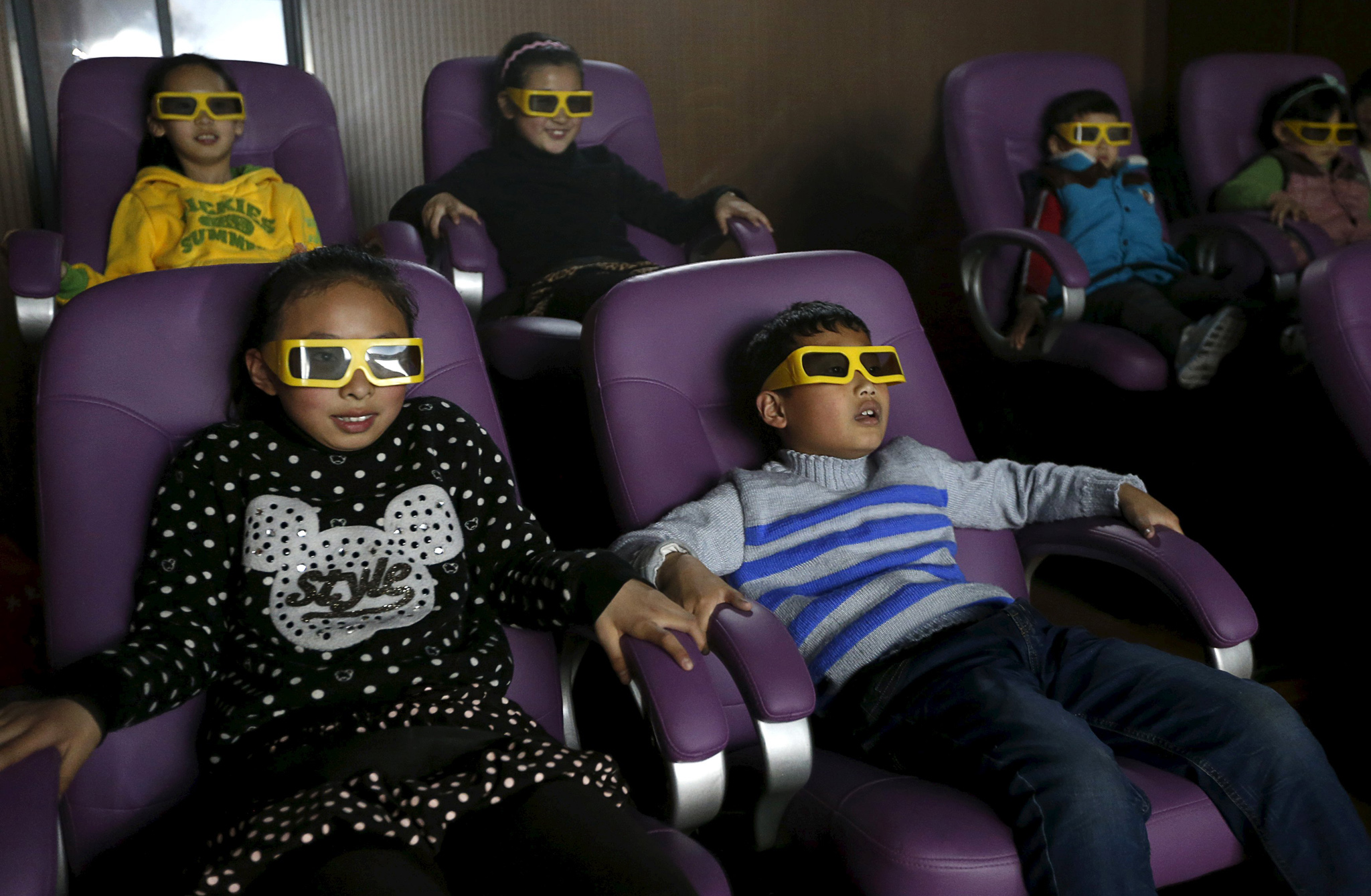 Children watch a 3D war movie at a community theatre in Hefei, Anhui province, China.