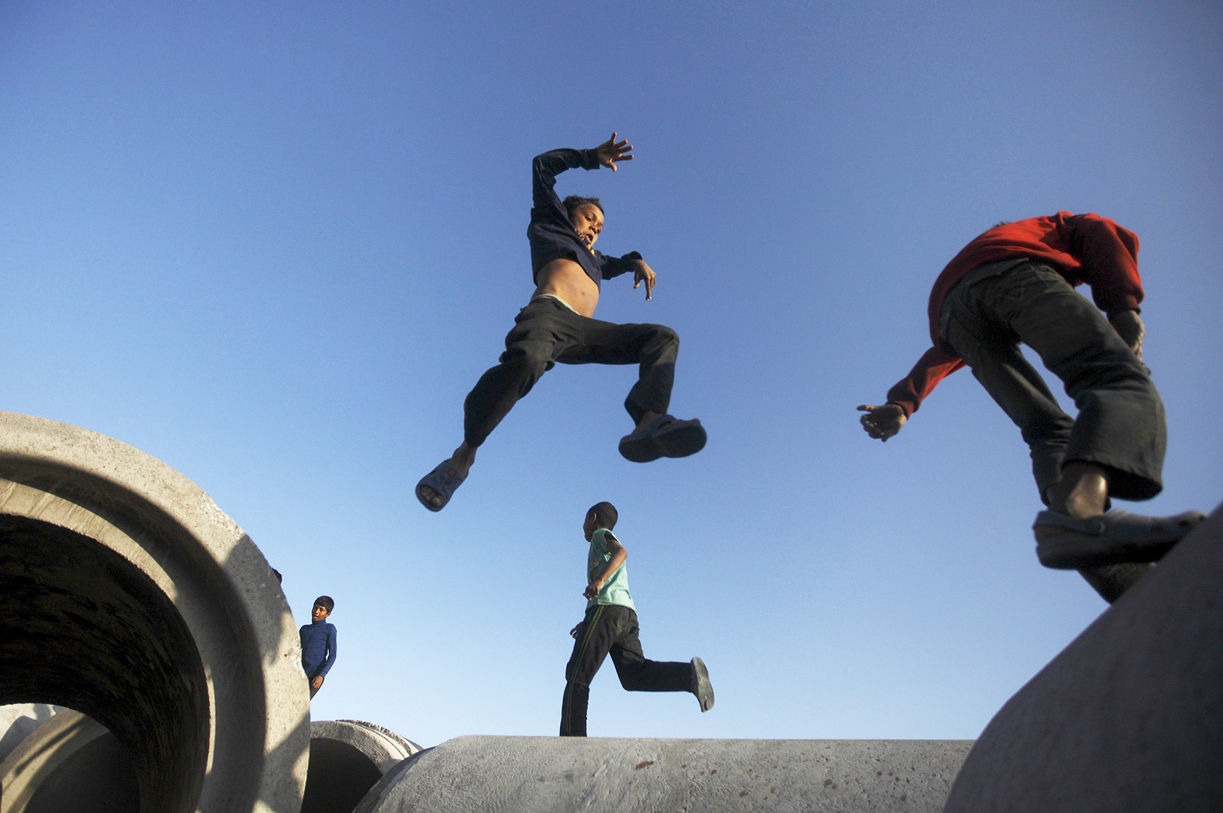 A boy from the slum jumps from one concrete drainage pipe to another along the bank of Bagmati River, in Kathmundu