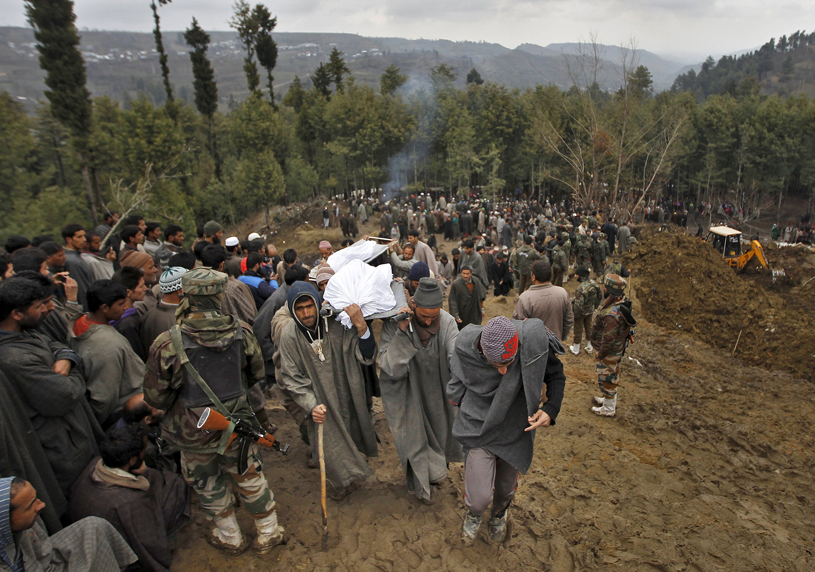 Kashmiri villagers carry the bodies of victims, who died after a hillside collapsed onto a house, for burial at Ledhan