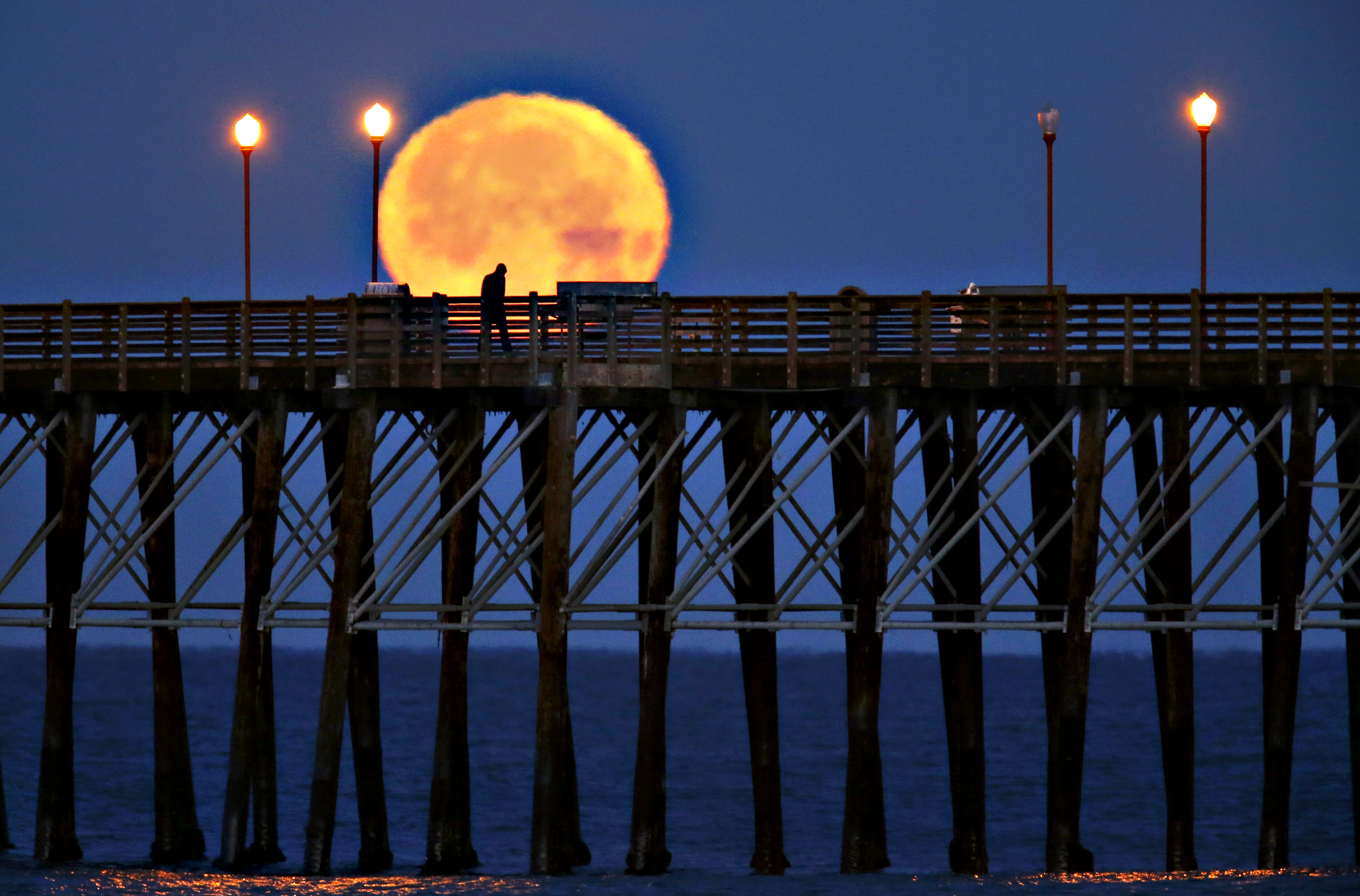 The moon sets in the early morning hours as a man walks along an ocean pier in Oceanside, California on Thursday