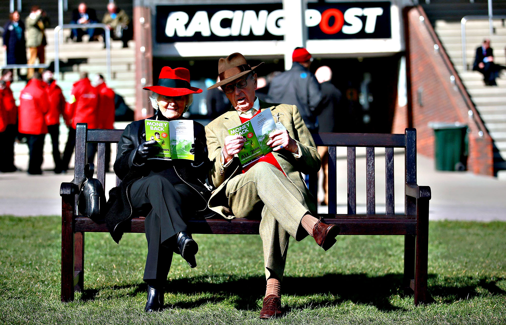 Race goers check the form on Champion Day, during the Cheltenham Festival at Cheltenham Racecourse. PRESS ASSOCIATION Photo. Picture date: Tuesday March 10, 2015.