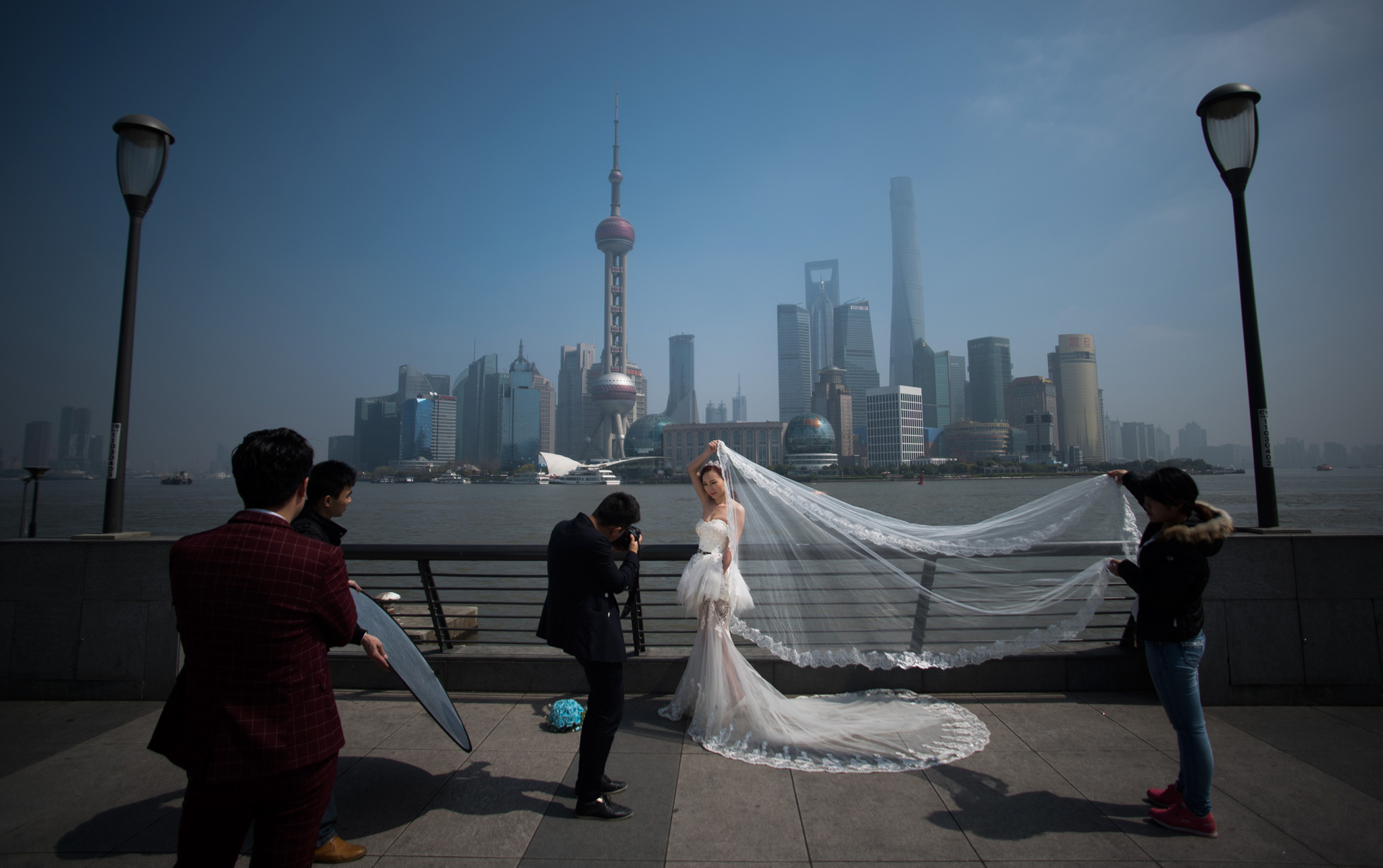 A woman poses for a wedding picture at the Bund in front of the financial district of Pudong in Shanghai on a sunny day on March