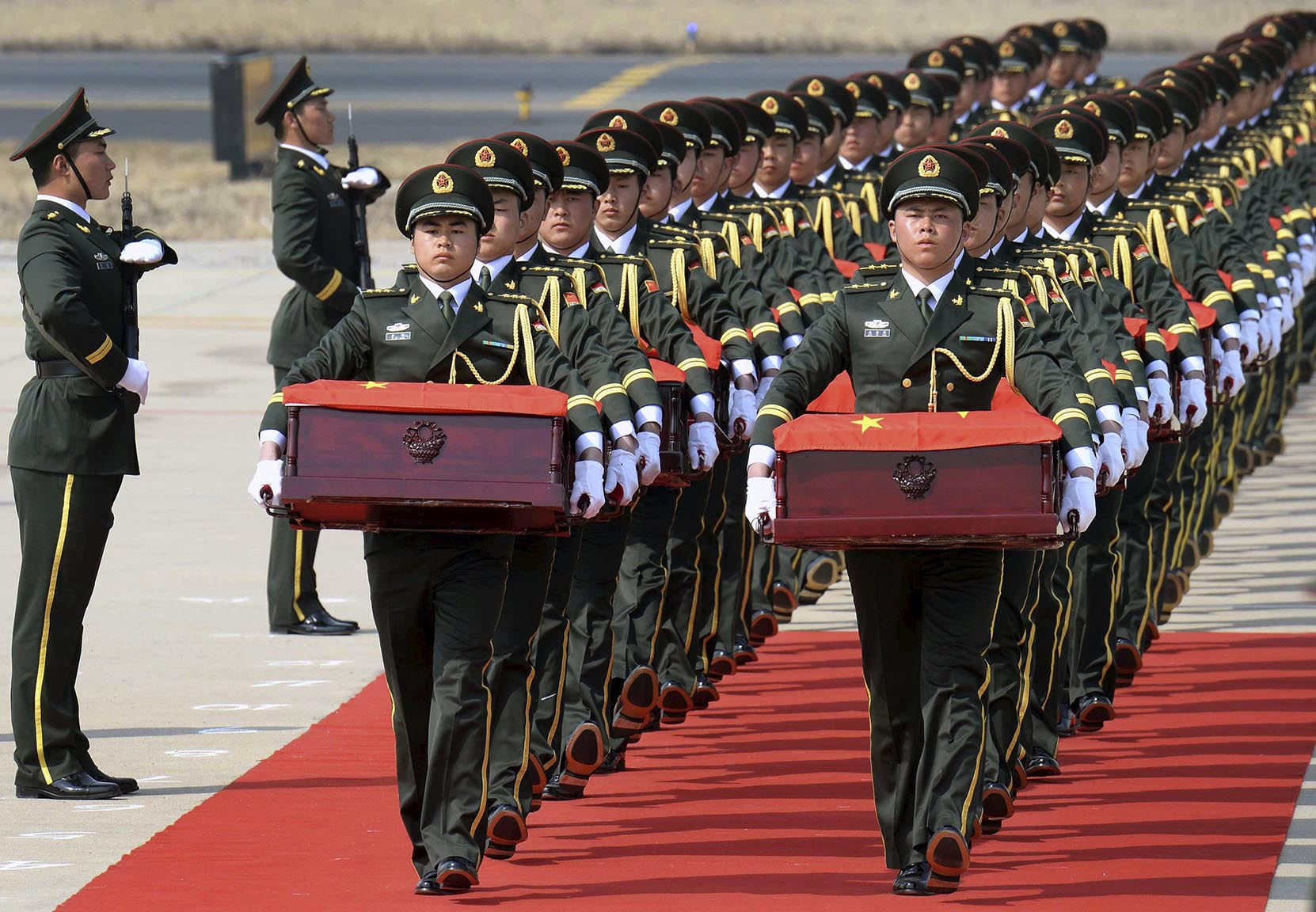Soldiers of the Chinese People's Liberation Army carry coffins containing remains of soldiers of the Chinese People's Volunteers who died in the Korean War, at the Taoxian International Airport of Shenyang